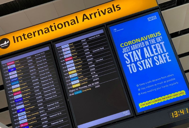 A public health campaign message is displayed on an arrivals information board at Heathrow Airport, following the outbreak of the coronavirus disease (COVID-19), London, Britain, July 29, 2020. REUTERS/Toby Melville/File Photo