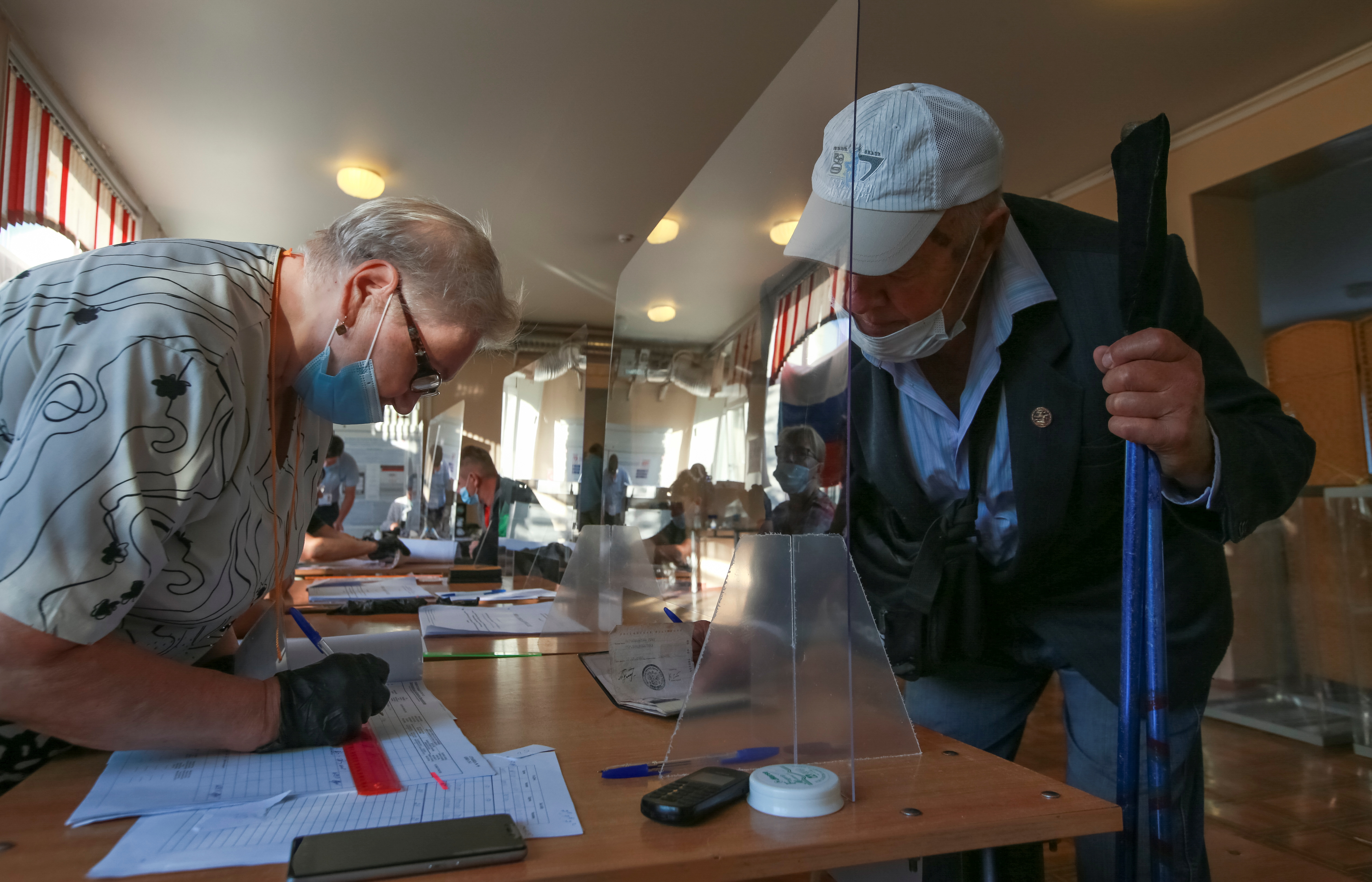 A voter receives his ballots at the last day of a three-day long parliamentary elections in the far eastern city of Vladivostok, Russia September 19, 2021.  REUTERS/Tatiana Meel