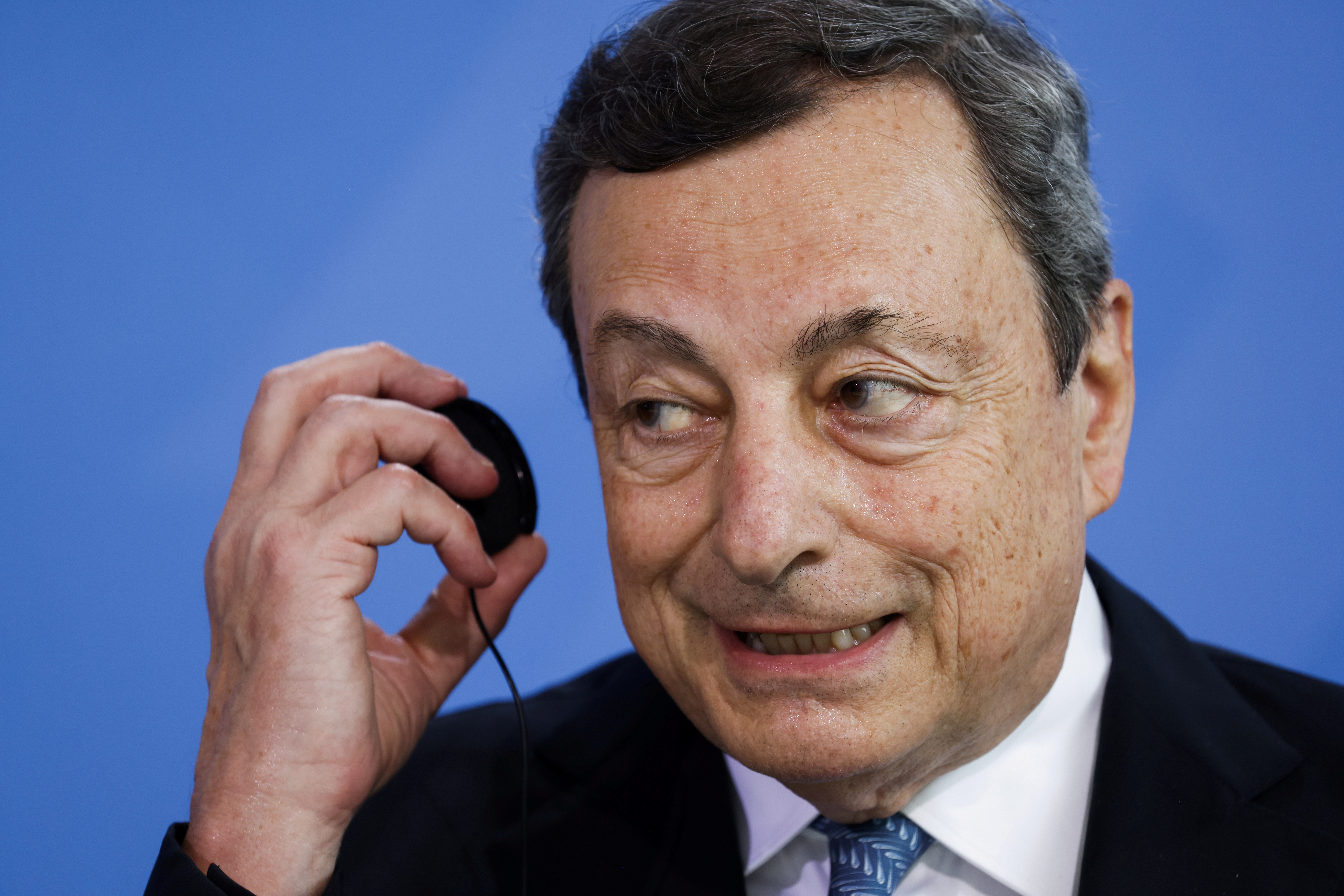 Italian Prime Minister Mario Draghi takes his headsets off after a news conference at the chancellery in Berlin, Germany, June 21, 2021.  Odd Andersen/Pool via REUTERS/File Photo