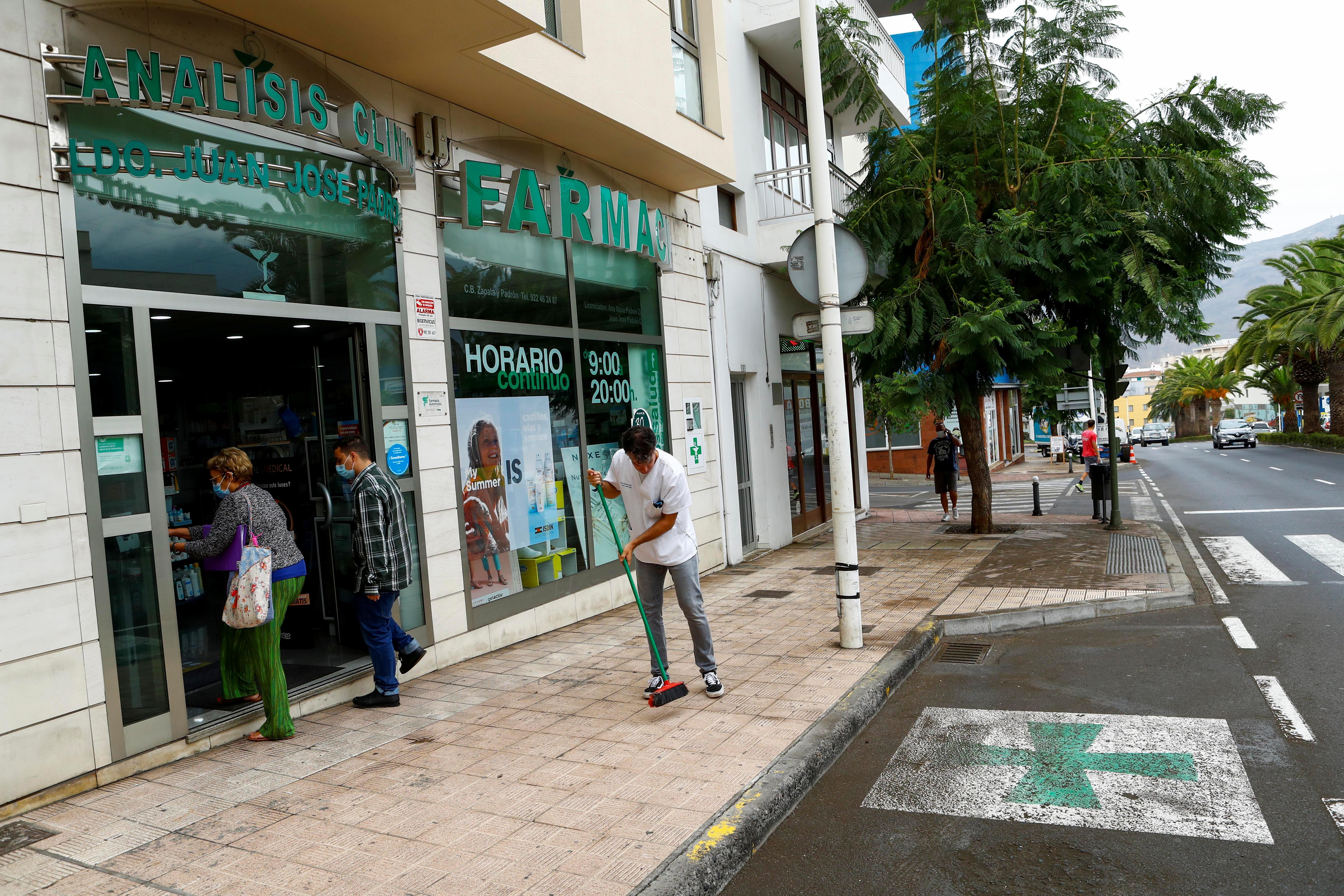 Victor Brito, a pharmacist, sweeps the sidewalk following the eruption of a volcano on the Island of La Palma, in Los Llanos de Aridane, Spain September 22, 2021. REUTERS/Borja Suarez