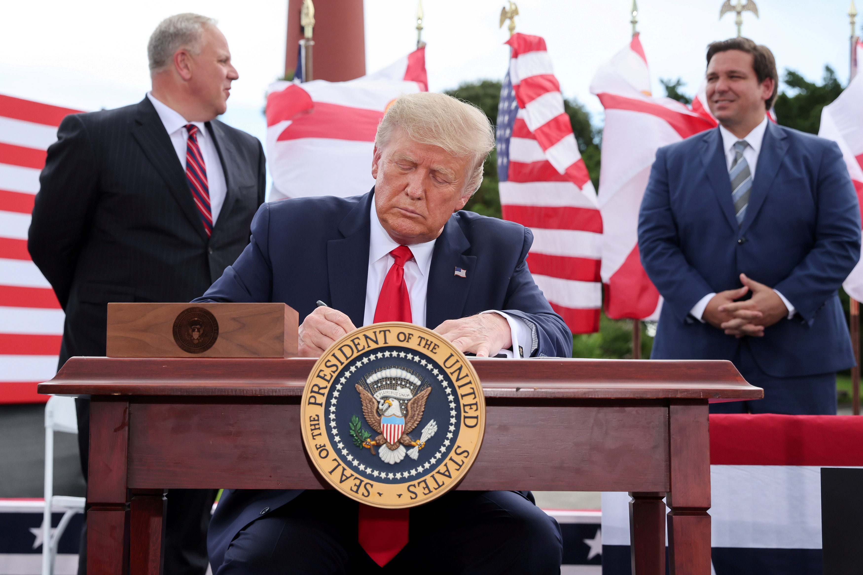 U.S. President Donald Trump signs an extension of the ban on offshore drilling off the coast of the state of Florida in front of a crowd of Trump supporters as U.S. Secretary of the Interior David Bernhardt and Florida Governor Ron DeSantis look on in Jupiter, Florida, U.S. September 8, 2020. REUTERS/Jonathan Ernst