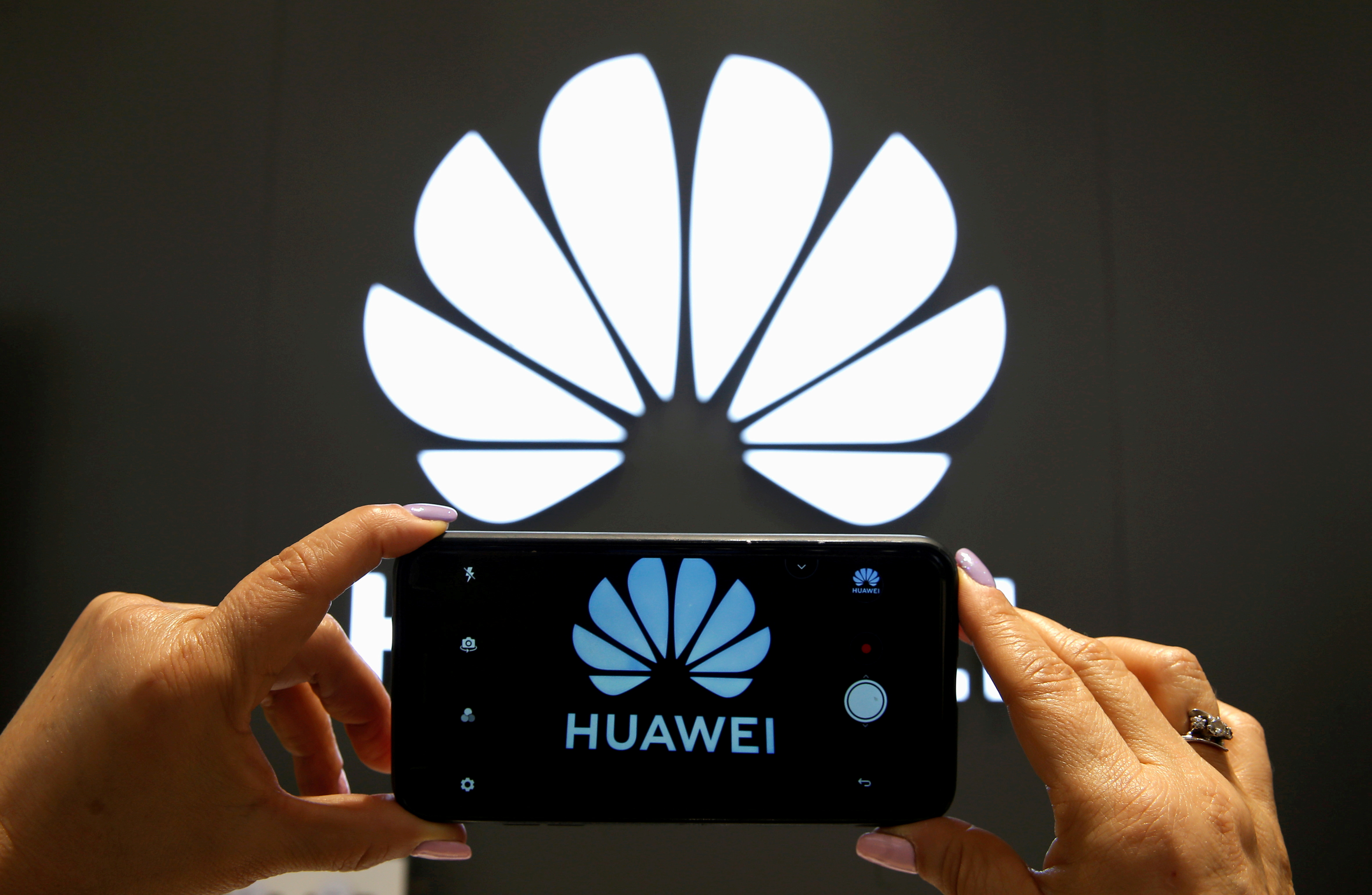 A Huawei logo is seen on a cell phone screen in their store at Vina del Mar, Chile. REUTERS/Rodrigo Garrido