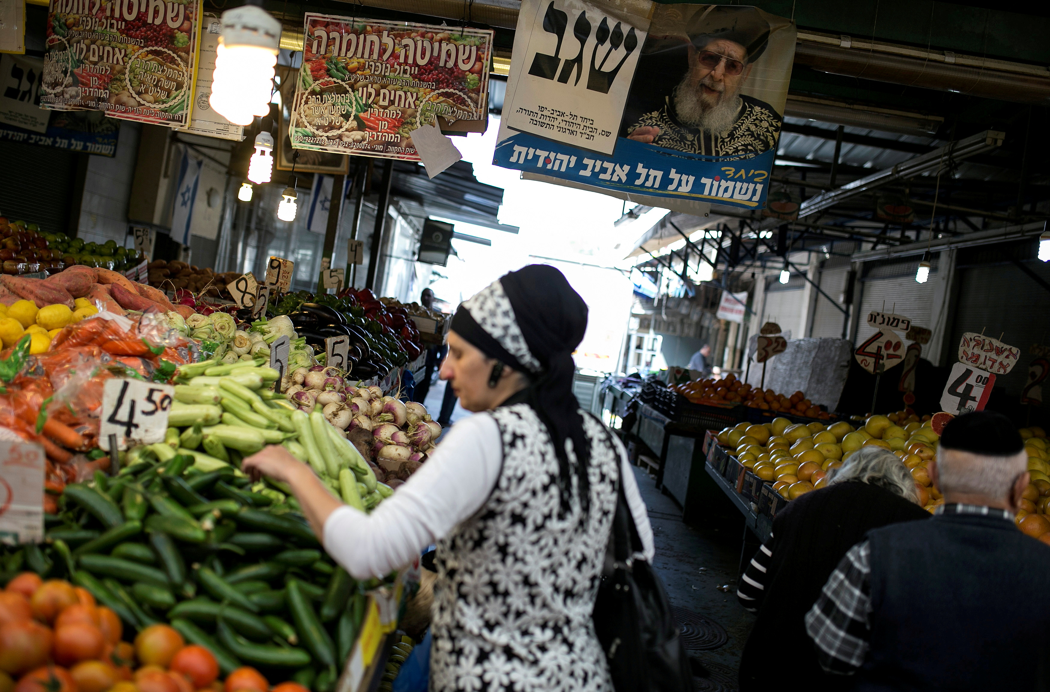 A religious Jewish woman shops for vegetables at a market in Tel Aviv, Israel March 10, 2015. REUTERS/Baz Ratner