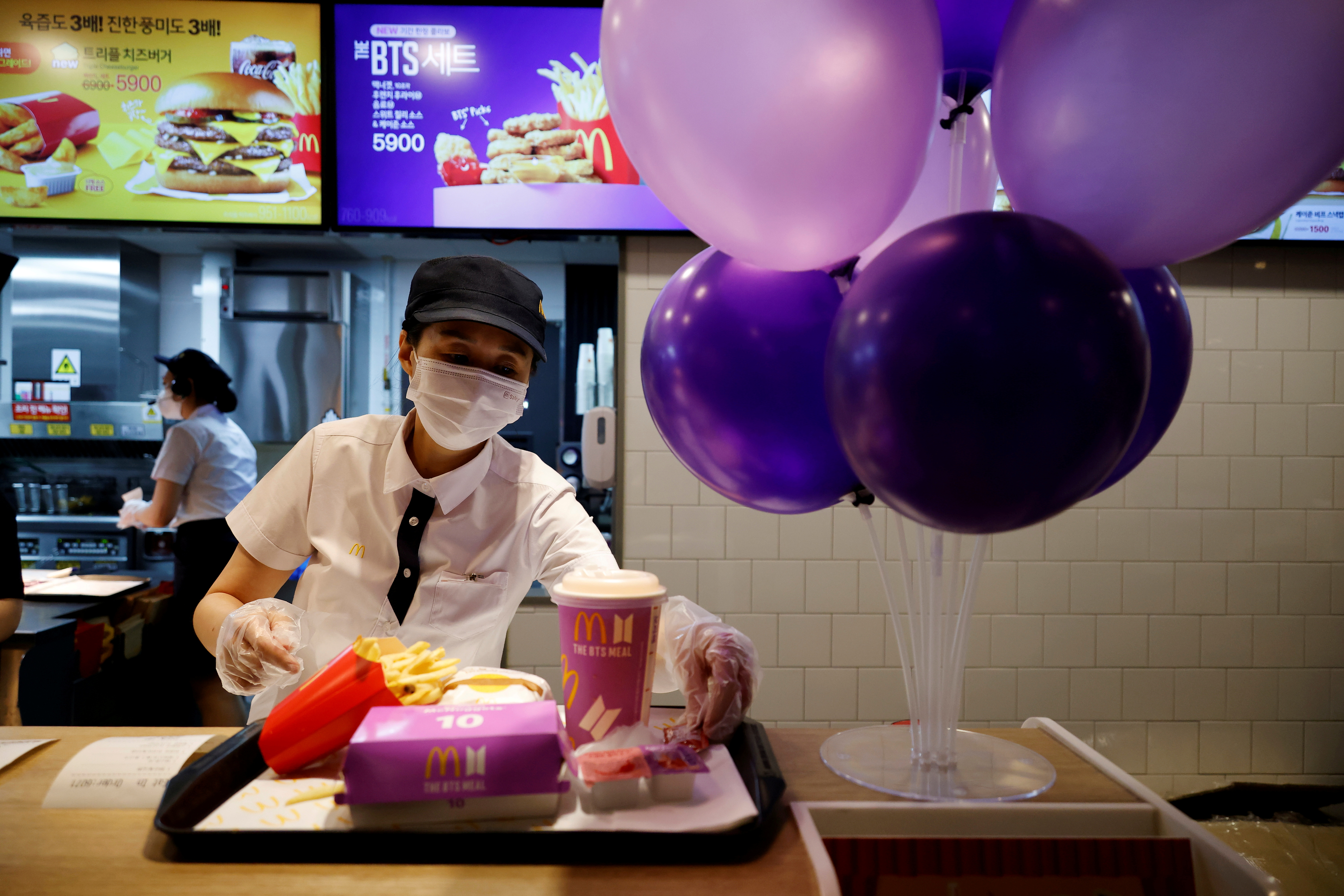 An employee of McDonald's serves a BTS meal, which is inspired and promoted by K-pop boy band BTS, during lunch hour at its restaurant in Seoul, South Korea, May 27, 2021.  REUTERS/Kim Hong-Ji/File Photo