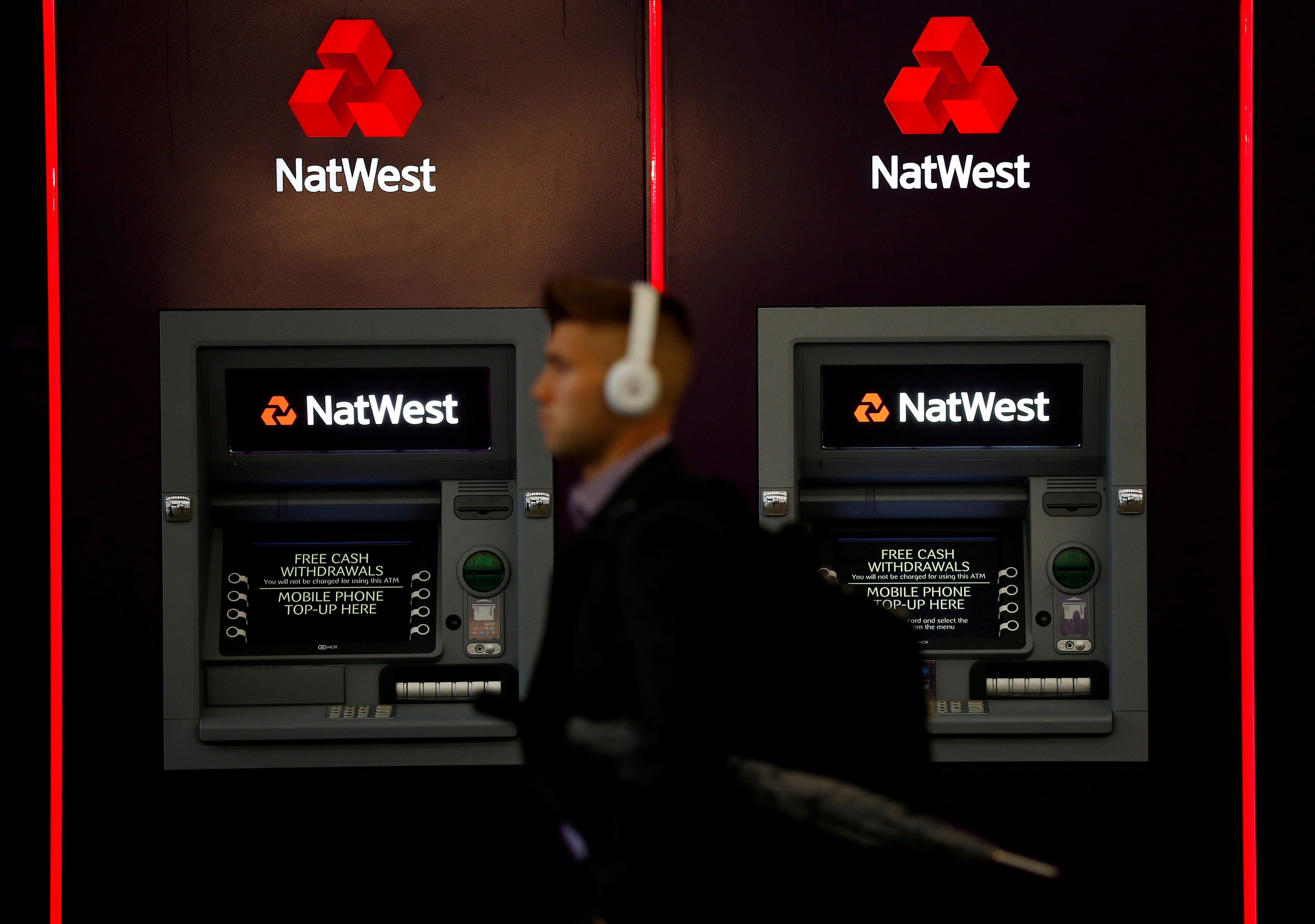 A man walks past ATM machines at branch of the NatWest bank in Manchester, Britain September 21, 2017. REUTERS/Phil Noble