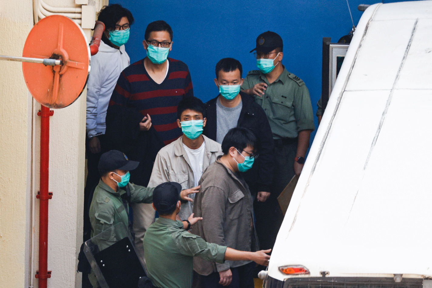 Pro-democracy activists Sam Cheung, Lam Cheuk-ting, Raymond Chan Chi-chuen and Owen Chow walk to a prison van to head to court, over national security law charges, in Hong Kong, China March 2, 2021. REUTERS/Tyrone Siu