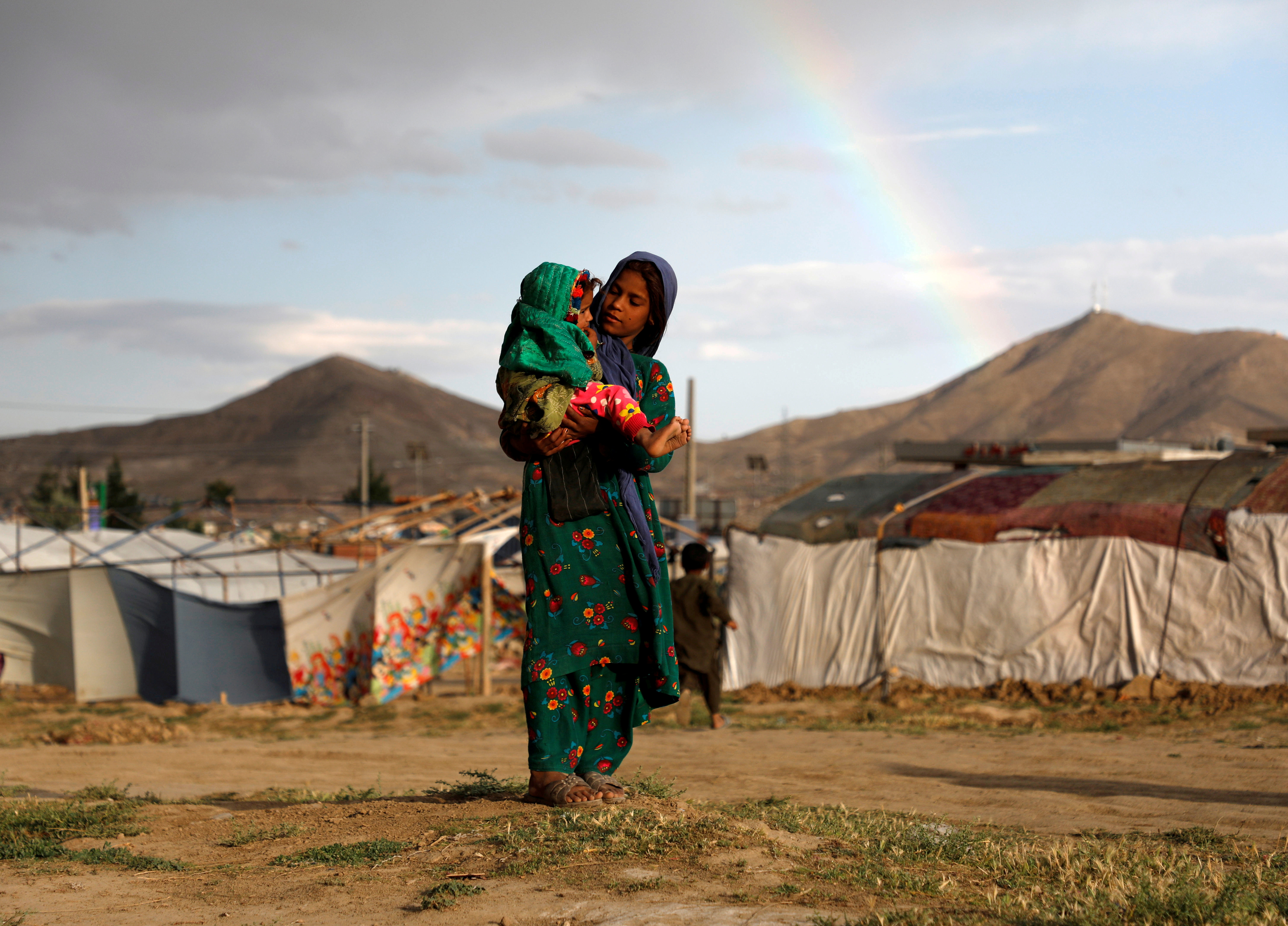 An internally displaced Afghan girl carries a child near their shelter at a camp on the outskirts of Kabul, Afghanistan June 20, 2019. REUTERS/Omar Sobhani