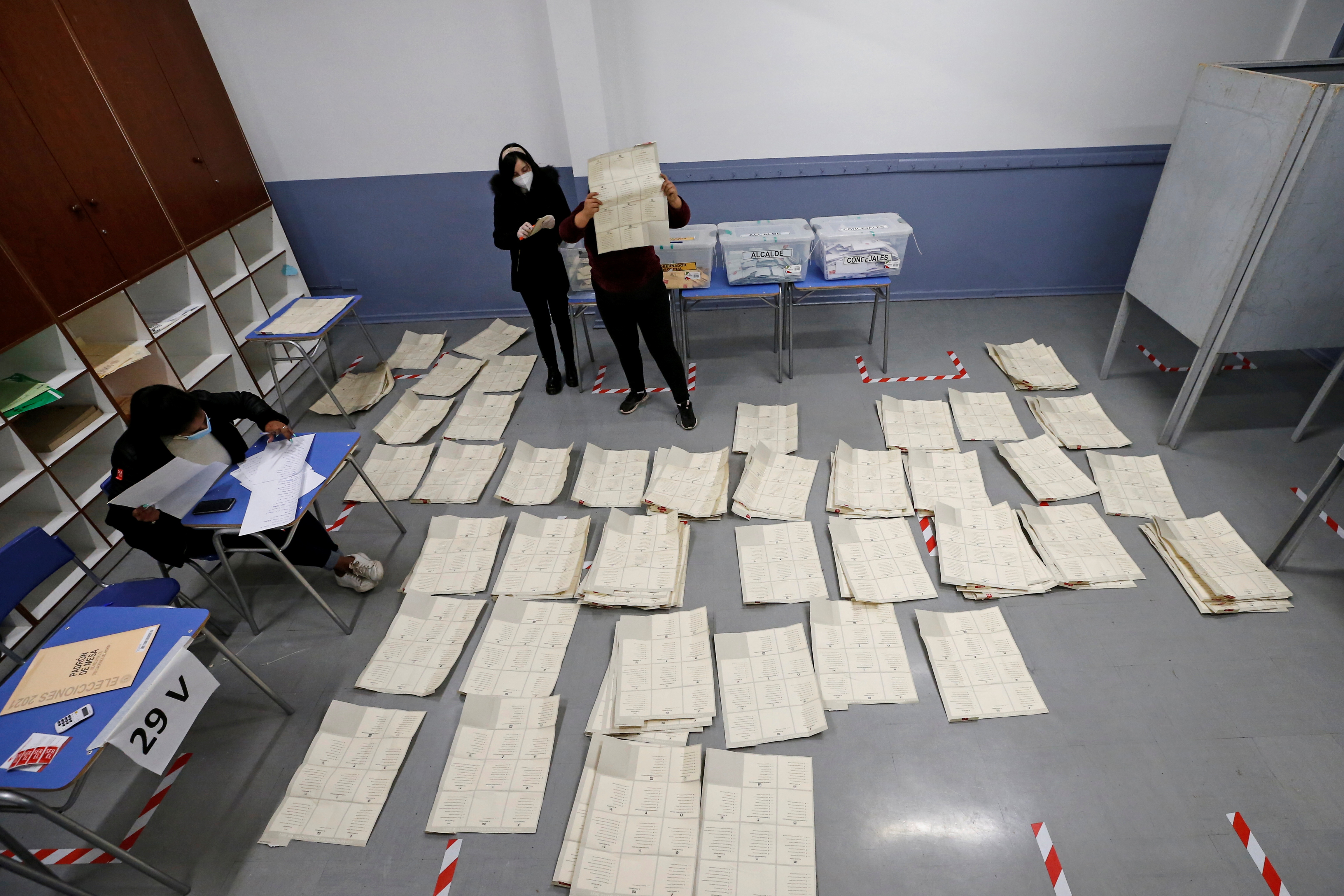 Poll workers sort through and count the votes after polls closed during the elections for governors, mayors, councillors and constitutional assembly members to draft a new constitution to replace Chile's charter, in Valparaiso, Chile, May 16, 2021. REUTERS/Rodrigo Garrido