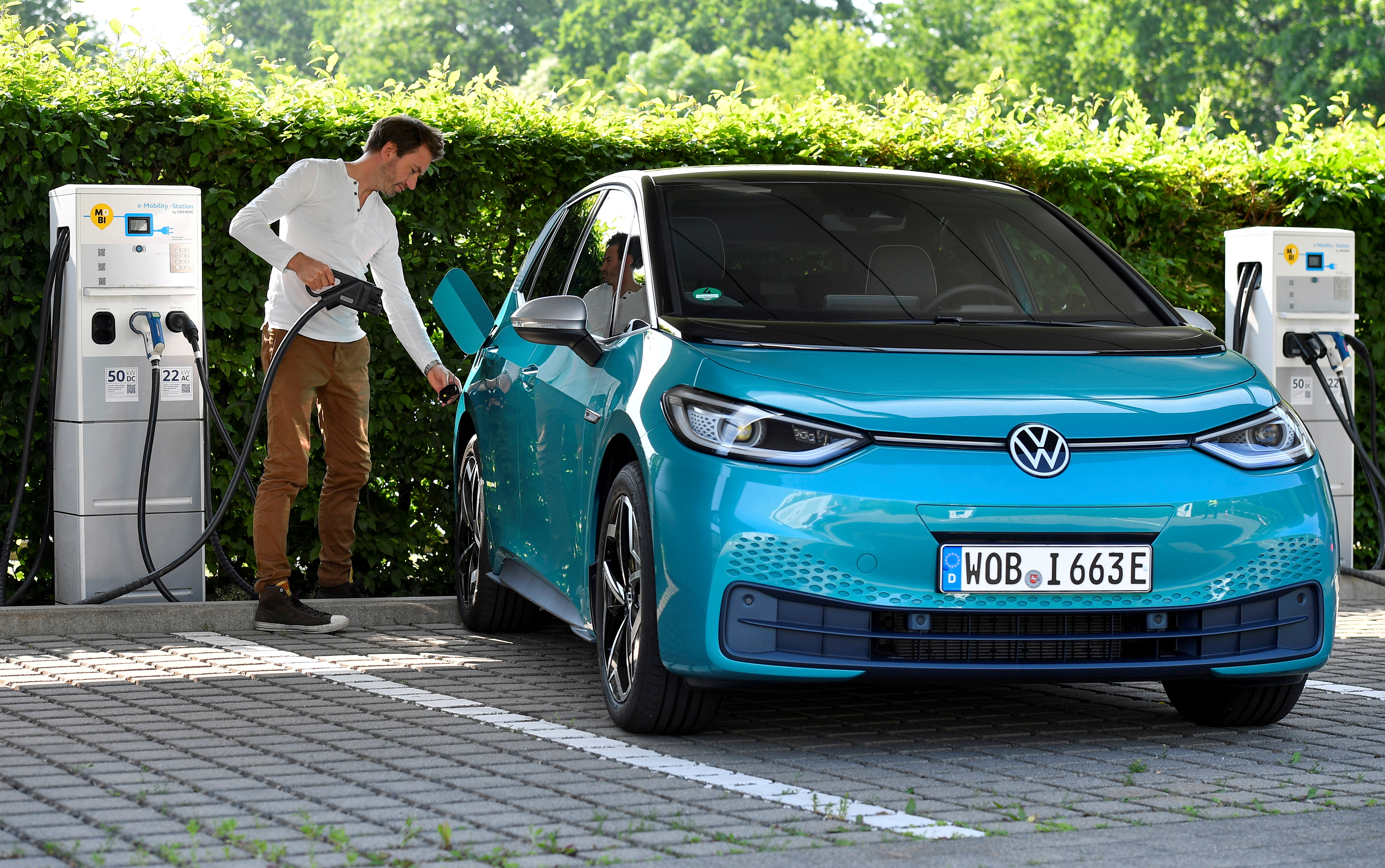 A man charges an electric ID. 3 car during a media event at German carmaker Volkswagen's so-called glass manufactory in Dresden, Germany, June 8, 2021. REUTERS/Matthias Rietschel