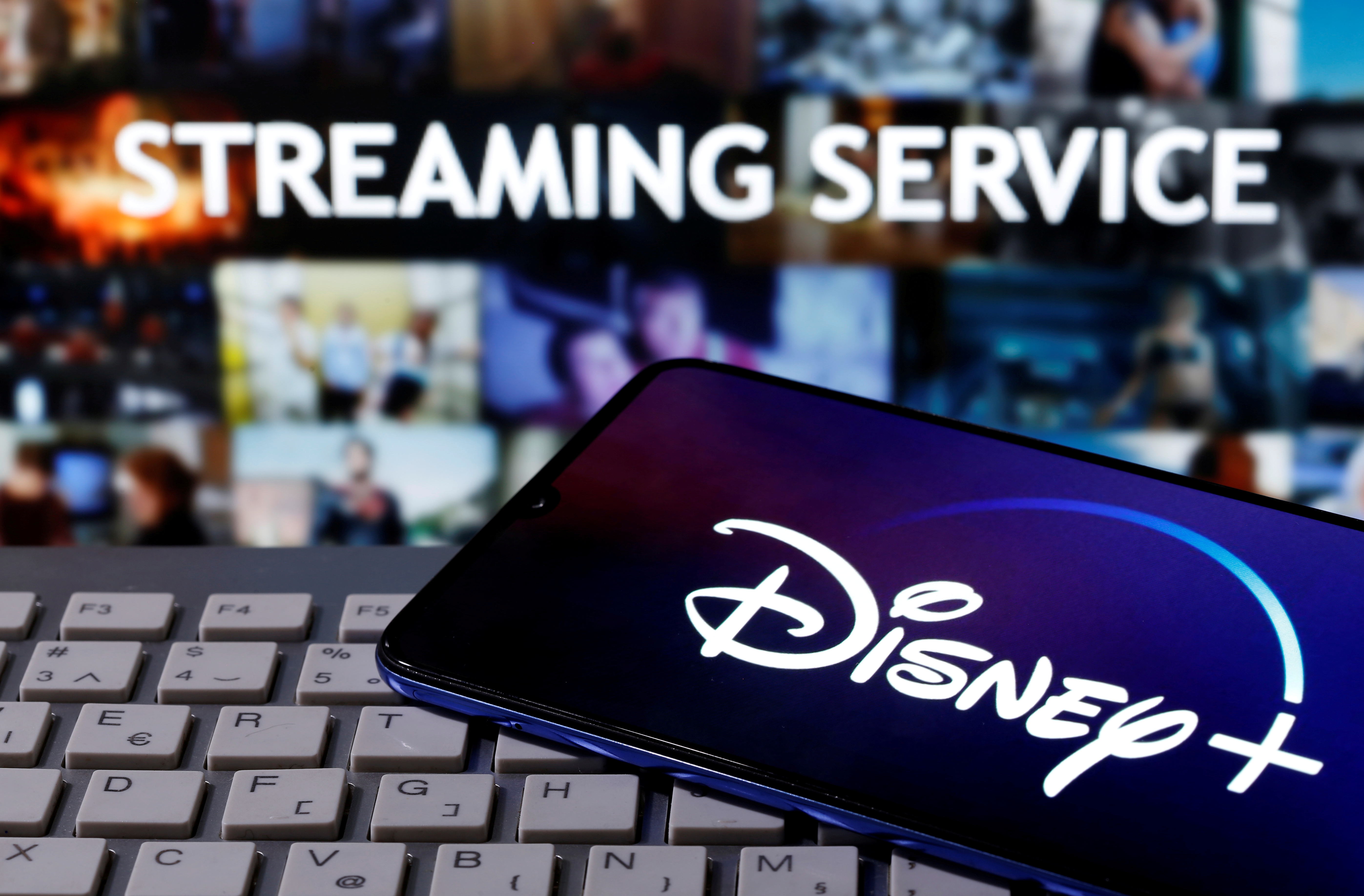 """A smartphone with displayed """"Disney"""" logo is seen on the keyboard in front of displayed """"Streaming service"""" words in this illustration taken March 24, 2020. REUTERS/Dado Ruvic"""