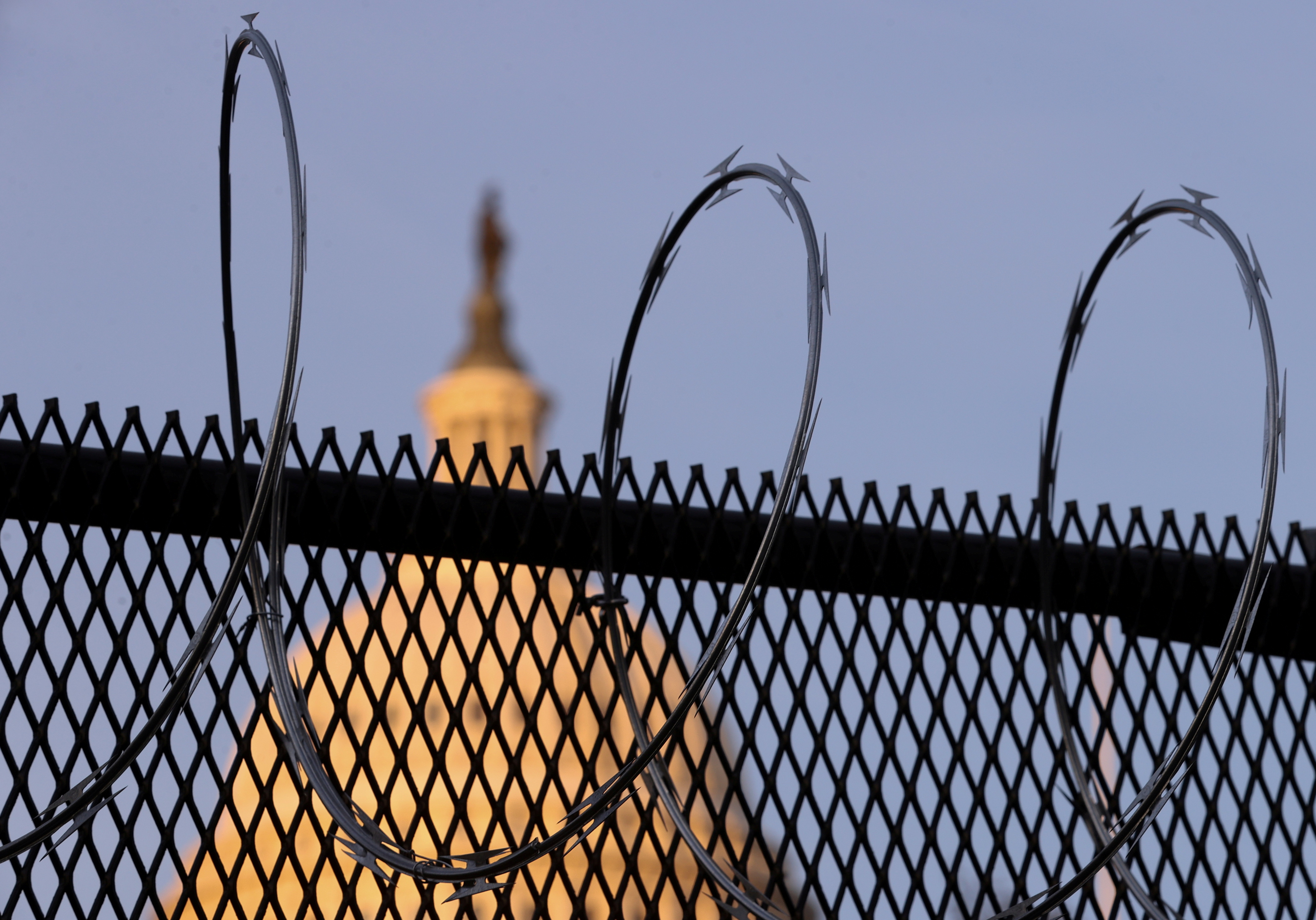 Newly-installed razor wire tops the unscalable fence surrounding the U.S. Capitol in the wake of the January 6th riot and ahead of the upcoming inauguration in Washington, U.S. January 14, 2021. REUTERS/Jonathan Ernst/File Photo