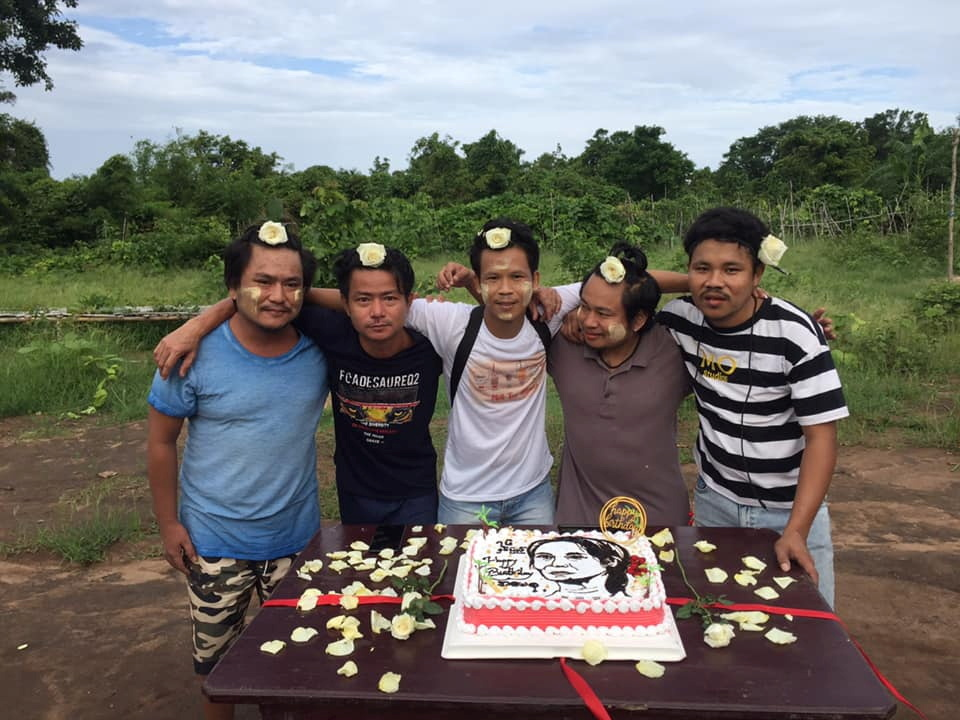 Men with flowers in their hair in support of Myanmar's detained leader, Aung San Suu Kyi, pose next to the cake with frosting imprint of her face to mark her birthday, in Myanmar, June 19, 2021 in this picture obtained by Reuters