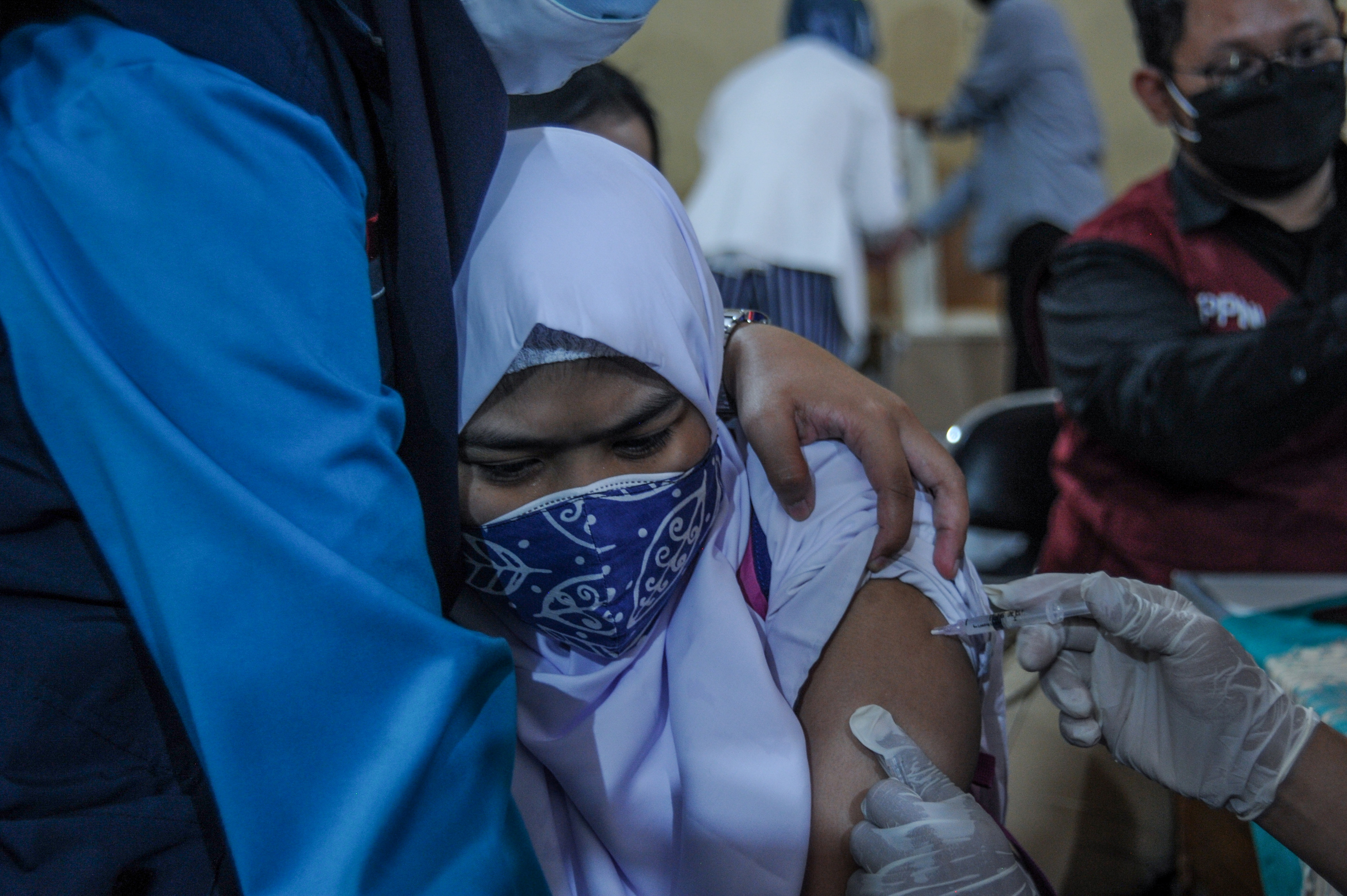 A student reacts as she receives a vaccine against the coronavirus disease (COVID-19) during a mass vaccination program for students as COVID-19 cases surge, in Bandung, West Java Province Indonesia July 14, 2021. Antara Foto/Raisan Al Farisi/via REUTERS