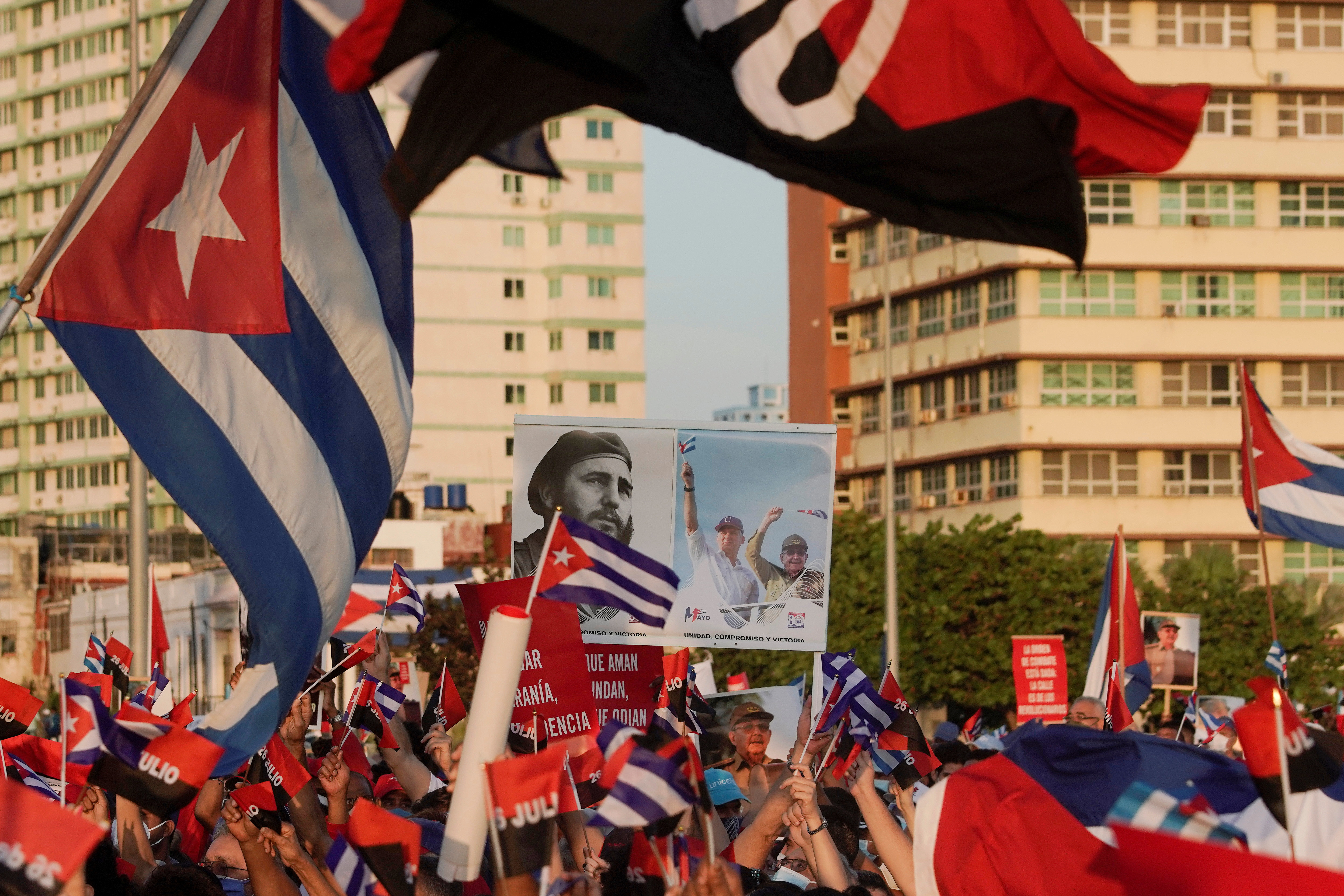 People carry a poster with photographs of Cuba's late President Fidel Castro, Cuba's President and First Secretary of the Communist Party Miguel Diaz-Canel and Cuba's former President and First Secretary of the Communist Party Raul Castro during a rally in Havana, Cuba, July 17, 2021. REUTERS/Alexandre Meneghini