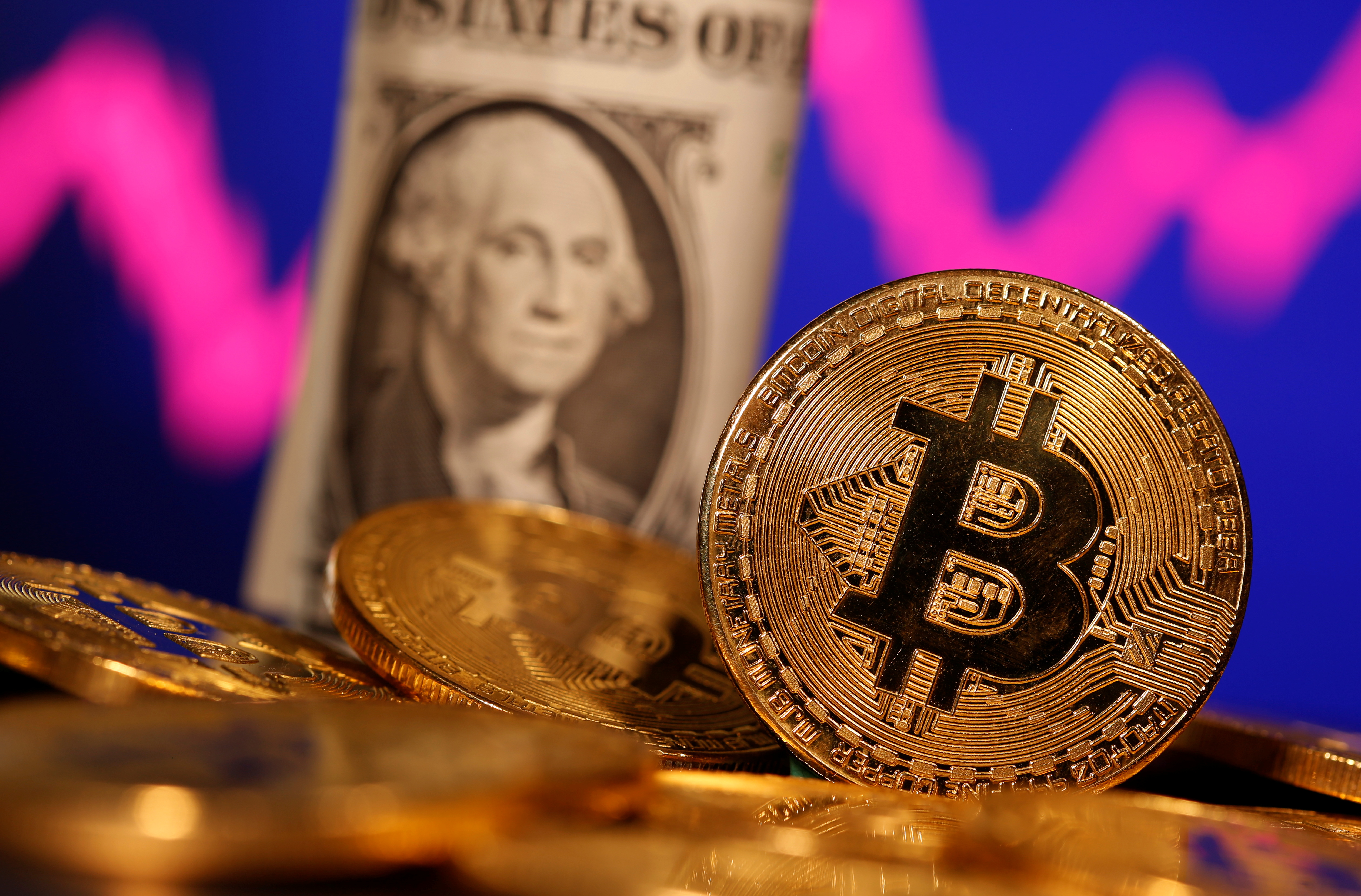 A representation of virtual currency Bitcoin and U.S. One Dollar banknote are seen in front of a stock graph in this illustration taken January 8, 2021. REUTERS/Dado Ruvic