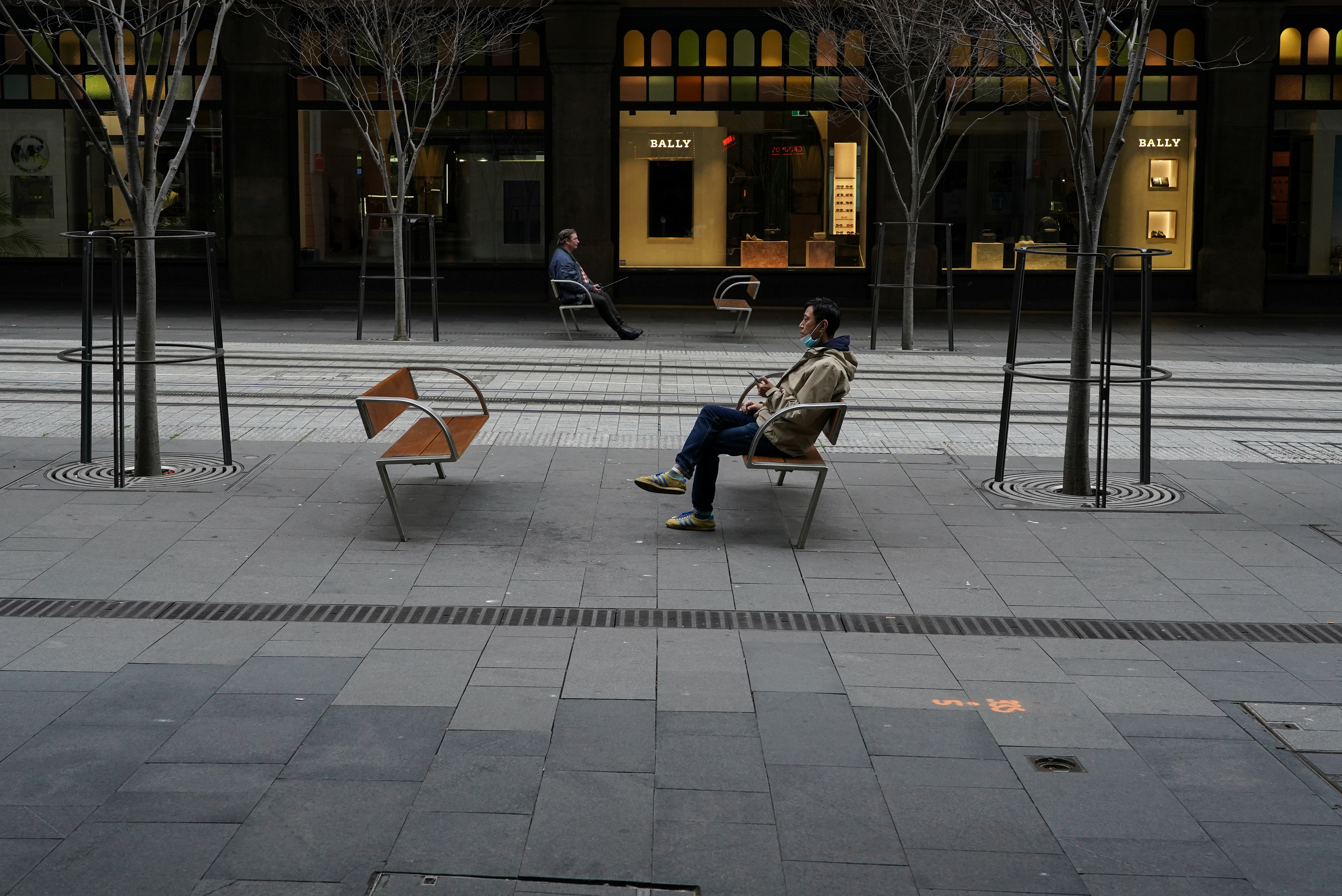 People sit with social distancing in the quiet city centre during a lockdown to curb the spread of a coronavirus disease (COVID-19) outbreak in Sydney, Australia, August 23, 2021.  REUTERS/Loren Elliott