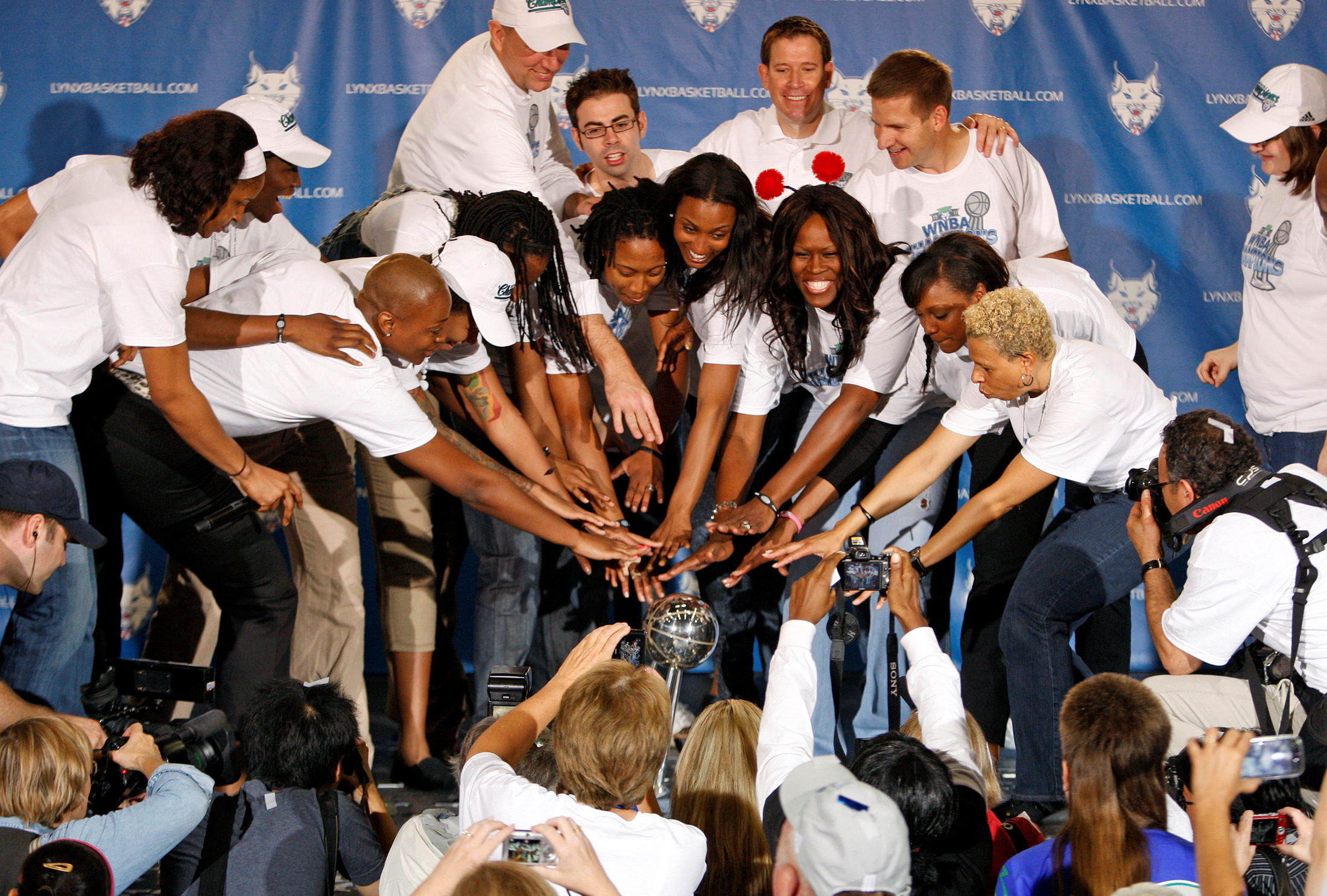 Members of the Minnesota Lynx basketball team motion to the championship trophy during a celebration of their WNBA Championship title in the Target Center in Minneapolis, October 11, 2011.       REUTERS/Eric Miller/File Photo