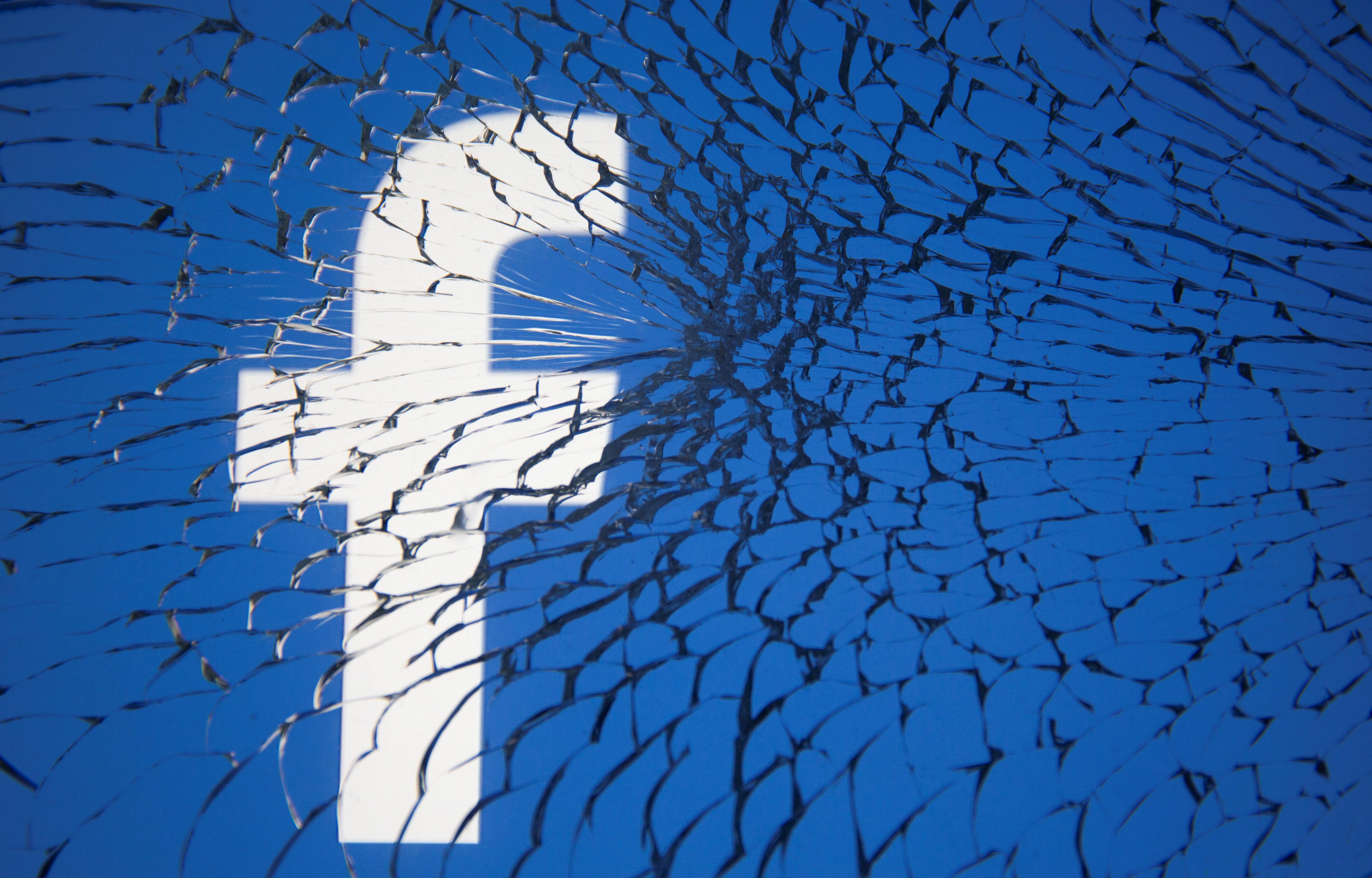 Facebook logo is displayed through broken glass in this illustration taken October 4, 2021. REUTERS/Dado Ruvic/Illustration