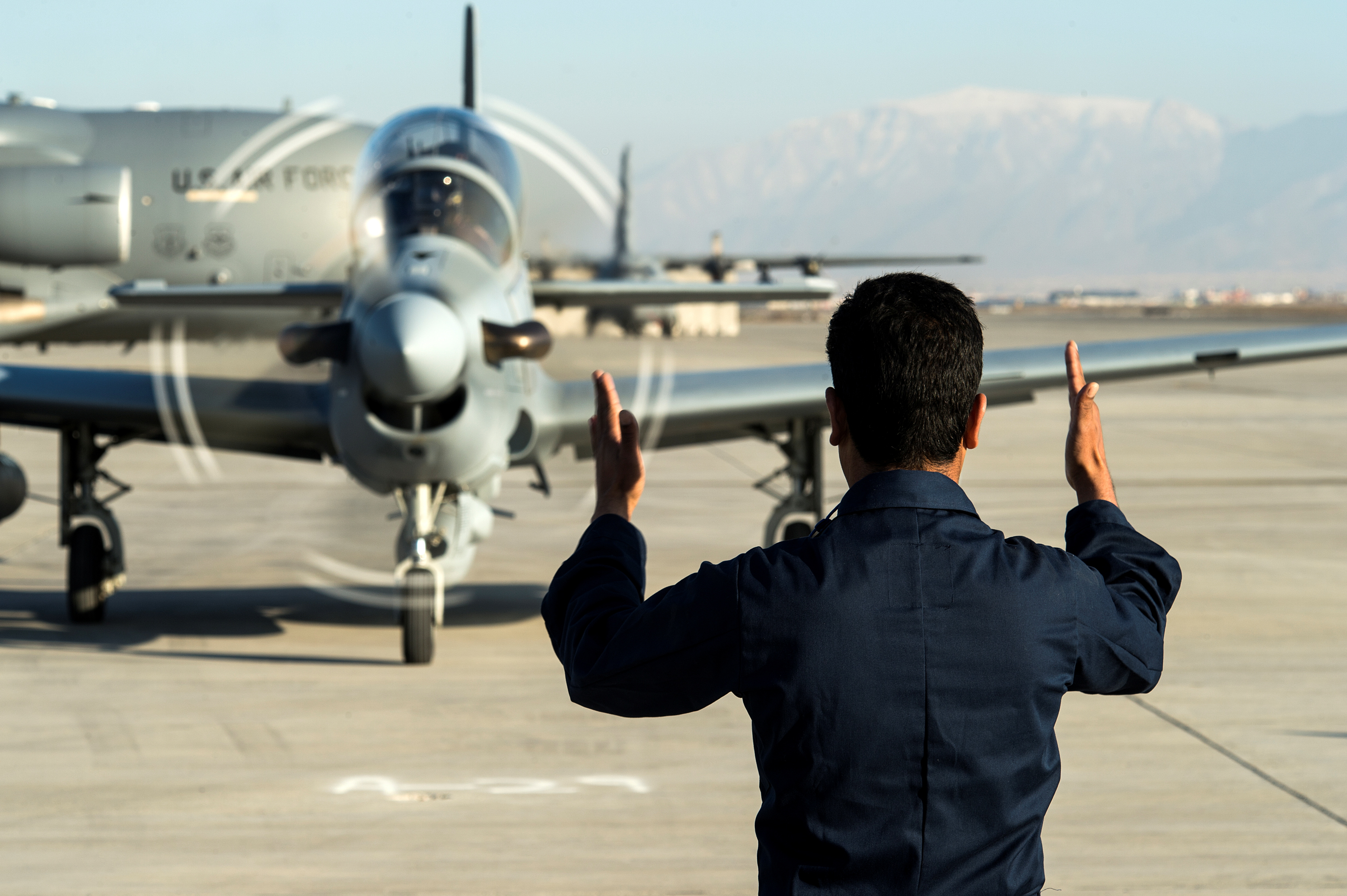 A member of the Afghan air force marshals in an A-29 Super Tucano at Hamid Karzai International Airport near Kabul, Afghanistan, January 15, 2016. Picture taken January 15, 2016. To match Special Report USA-AFGHANISTAN/PILOTS  U.S. Air Force/Tech. Sgt. Nathan Lipscomb/Handout via REUTERS