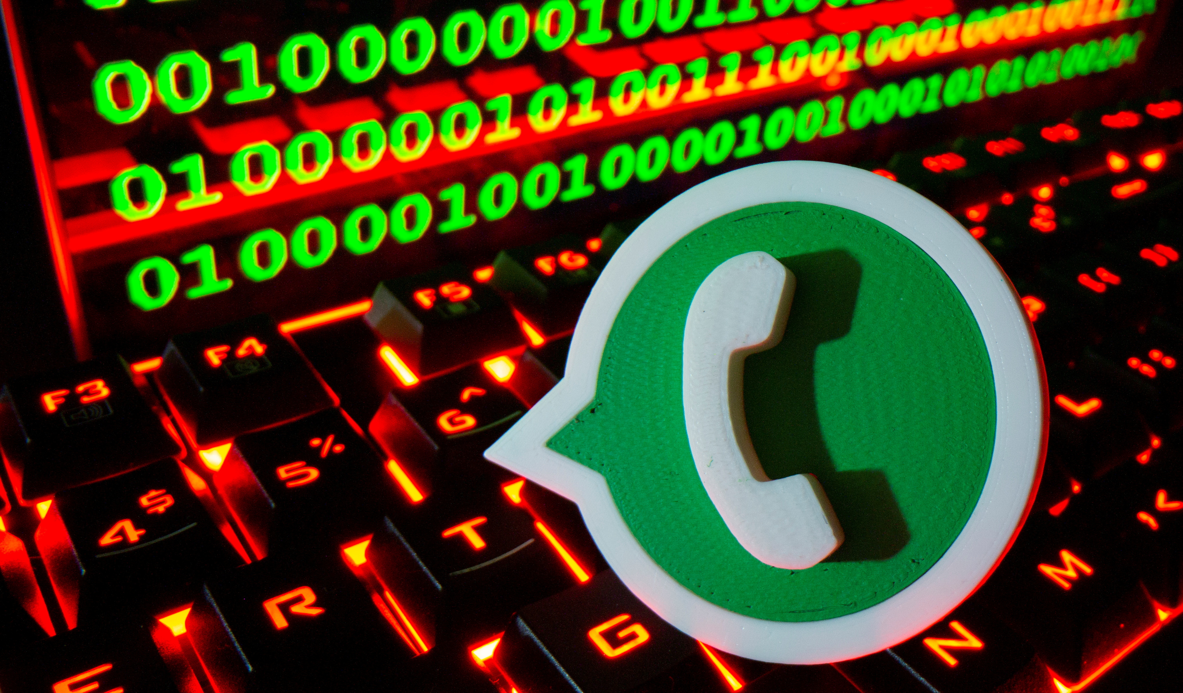 A 3D printed Whatsapp logo is pictured on a keyboard in front of binary code in this illustration taken September 24, 2021. REUTERS/Dado Ruvic/File Photo
