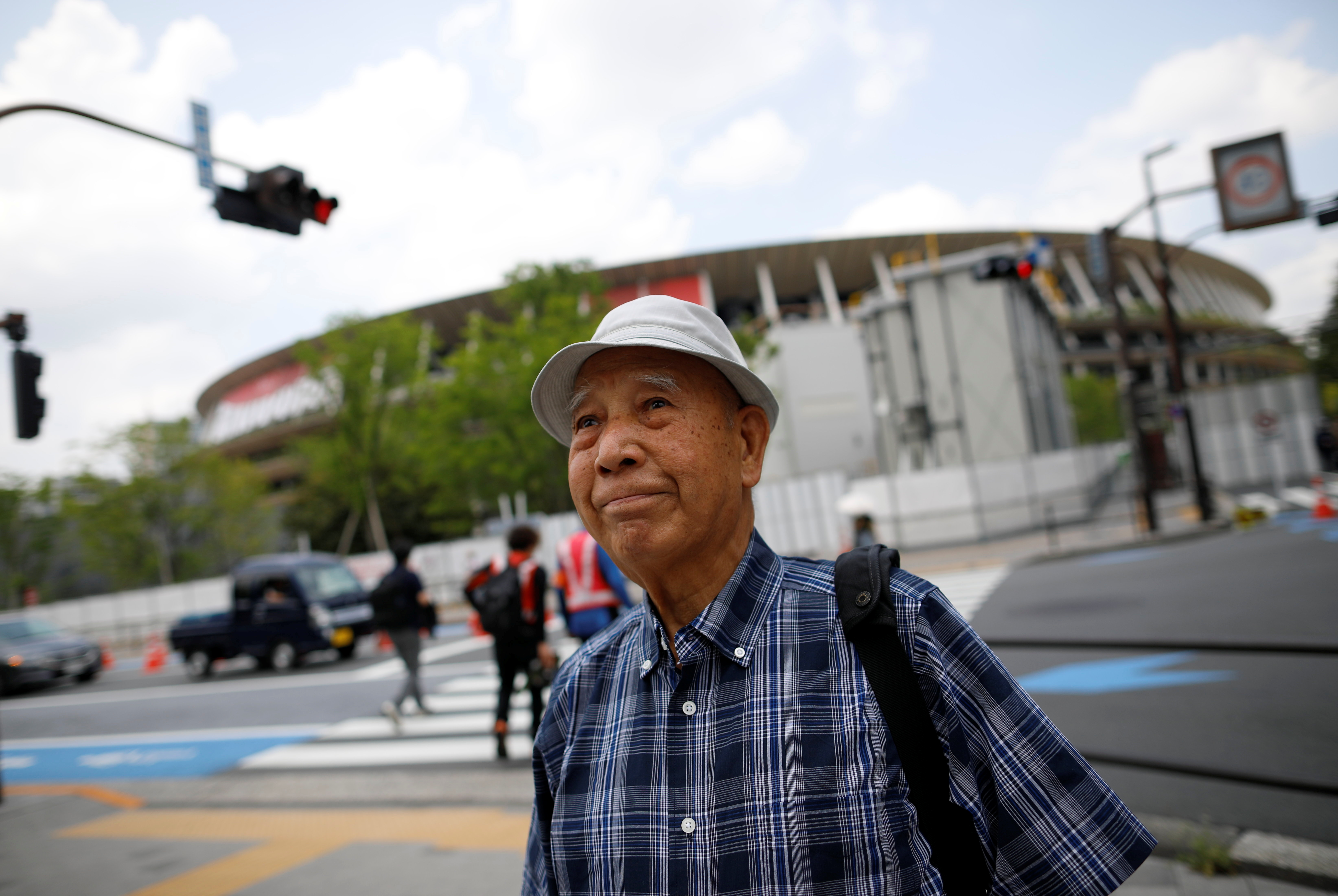 Kohei Jinno, 87, who was forced to leave his house two times ahead of the 1964 and 2020 Olympics Games to make way for construction of the main stadium, walks near the National Stadium, the main stadium for the 2020 Tokyo Olympic Games that have been postponed to 2021 due to the coronavirus disease (COVID-19) pandemic, in Tokyo, Japan June 24, 2021.  REUTERS/Issei Kato