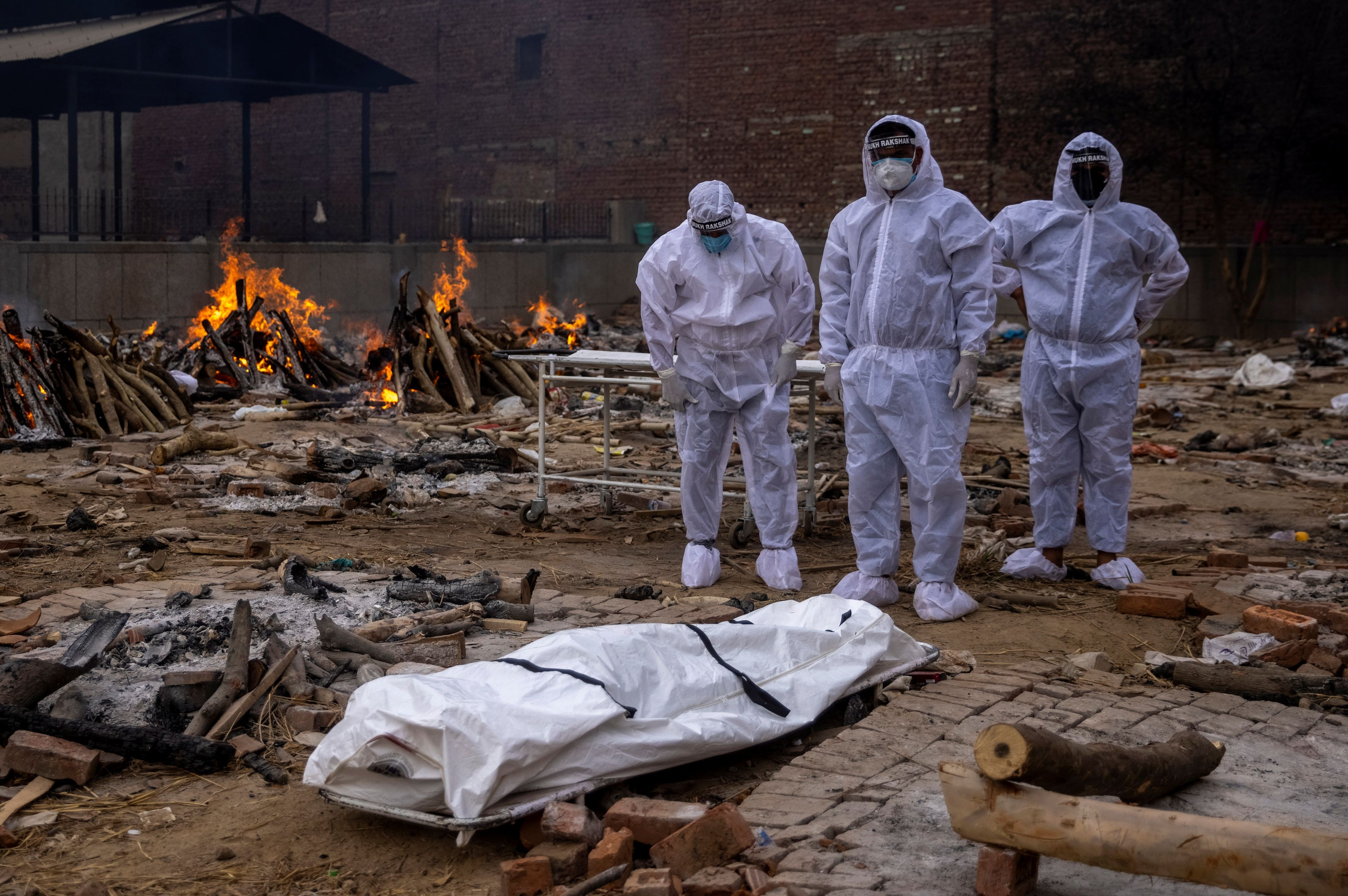 Men wearing protective suits stand next to the body of their relative, who died from the coronavirus disease (COVID-19), before her cremation at a crematorium ground in New Delhi, India, May 4, 2021. REUTERS/Danish Siddiqui