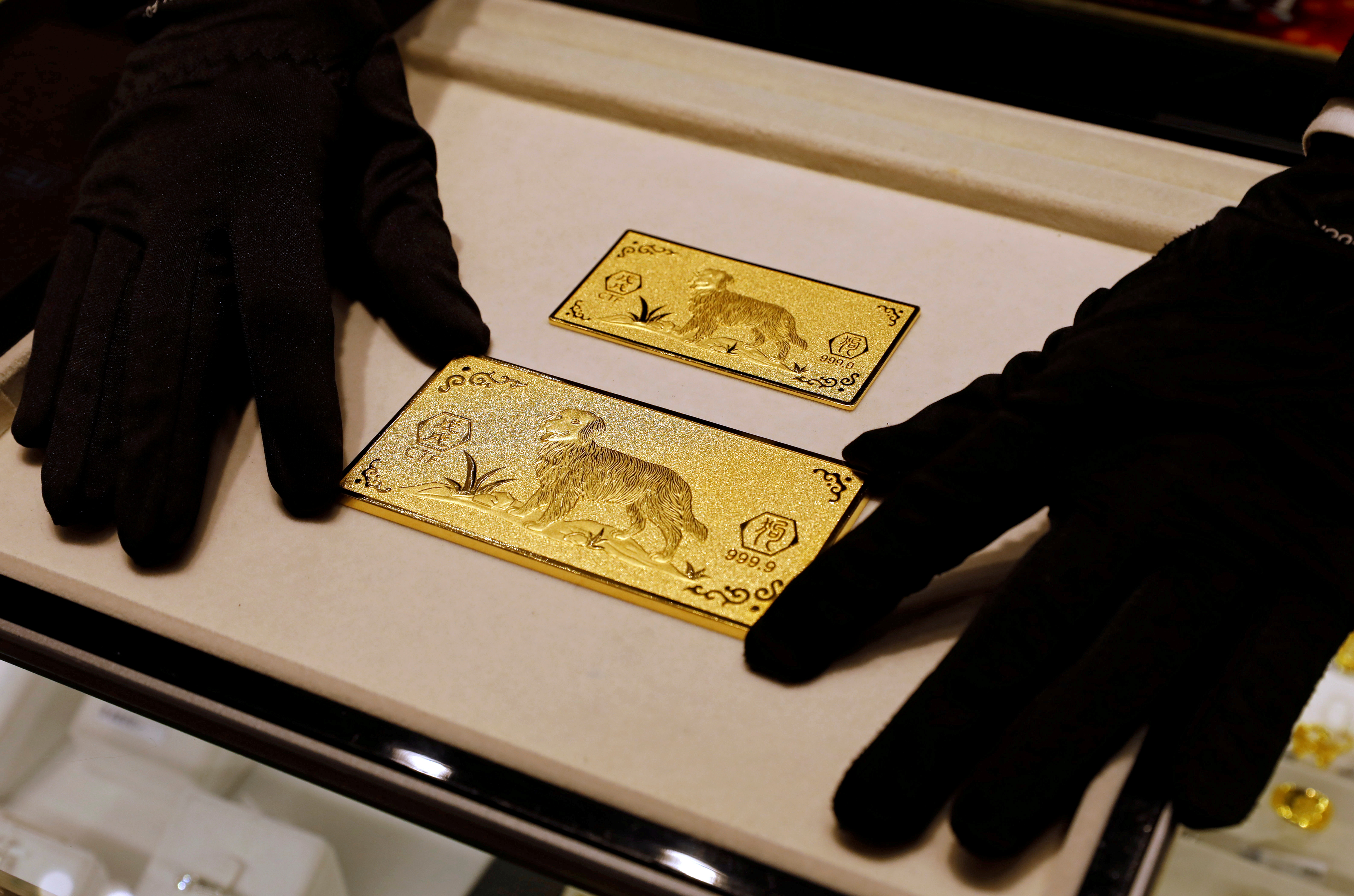 A salesperson arranges 24K gold bars engraved with dogs at Chow Tai Fook Jewellery store ahead of the Lunar Year of the Dog in Hong Kong, China December 14, 2017. REUTERS/Tyrone Siu