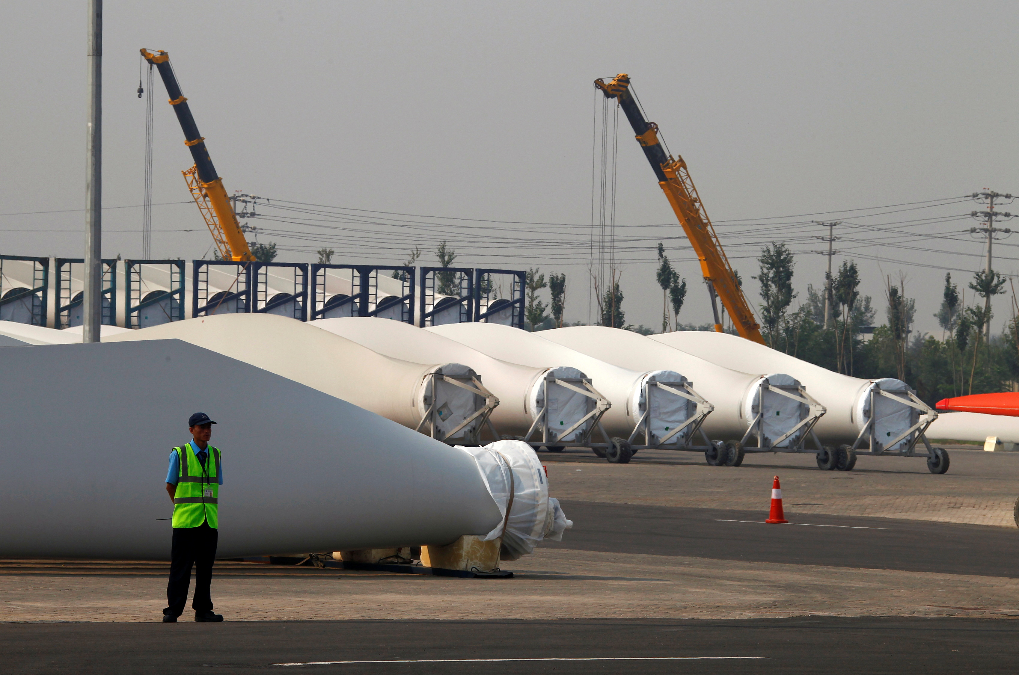 A security guard stands next to blades and bases for wind turbines in the grounds of the Vestas Wind Technology company's factory, located in the northern Chinese city of Tianjin September 14, 2010. REUTERS/David Gray