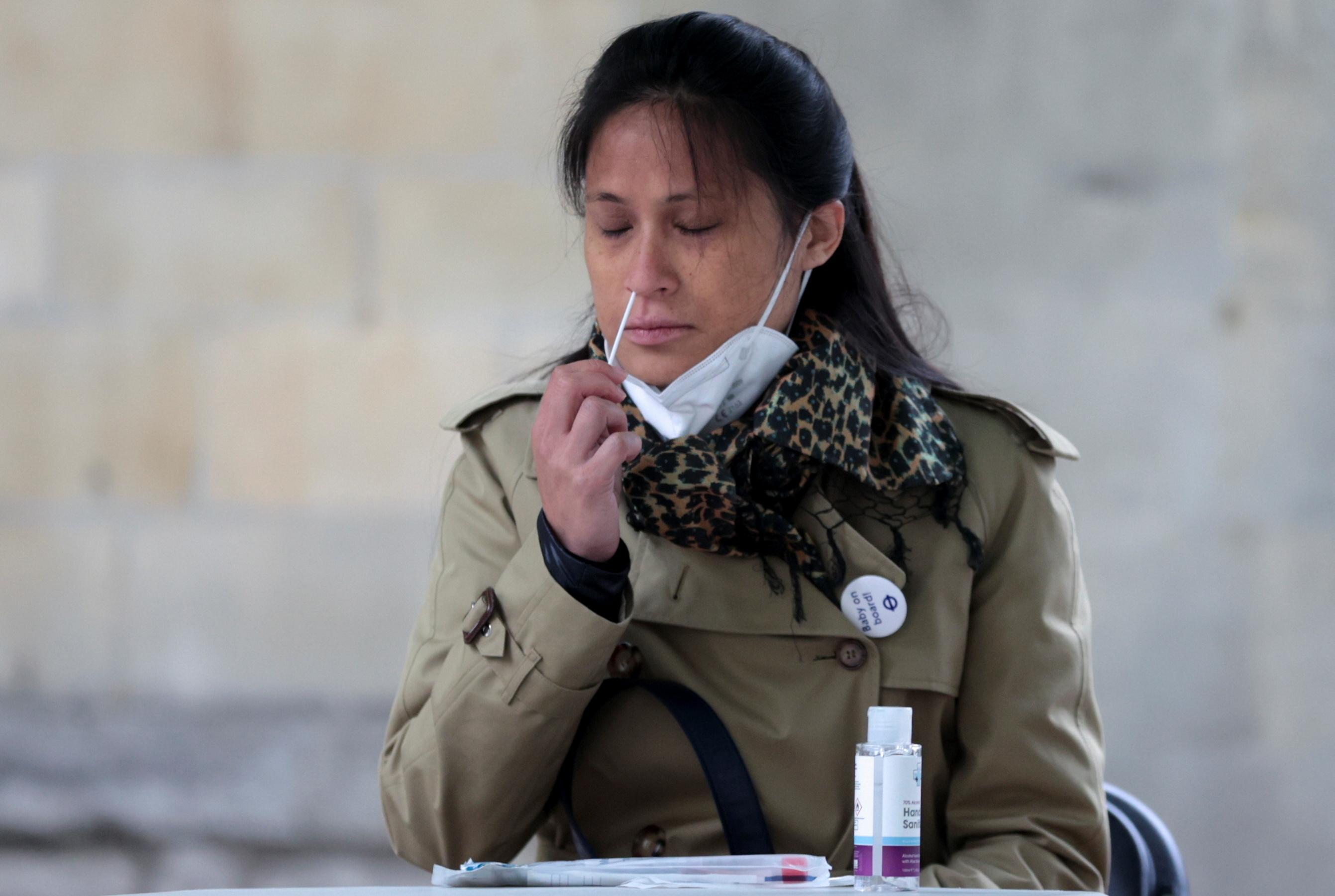 A woman takes a swab sample for the coronavirus disease (COVID-19) at a surge testing site in London, Britain, May 14, 2021. REUTERS/Hannah McKay