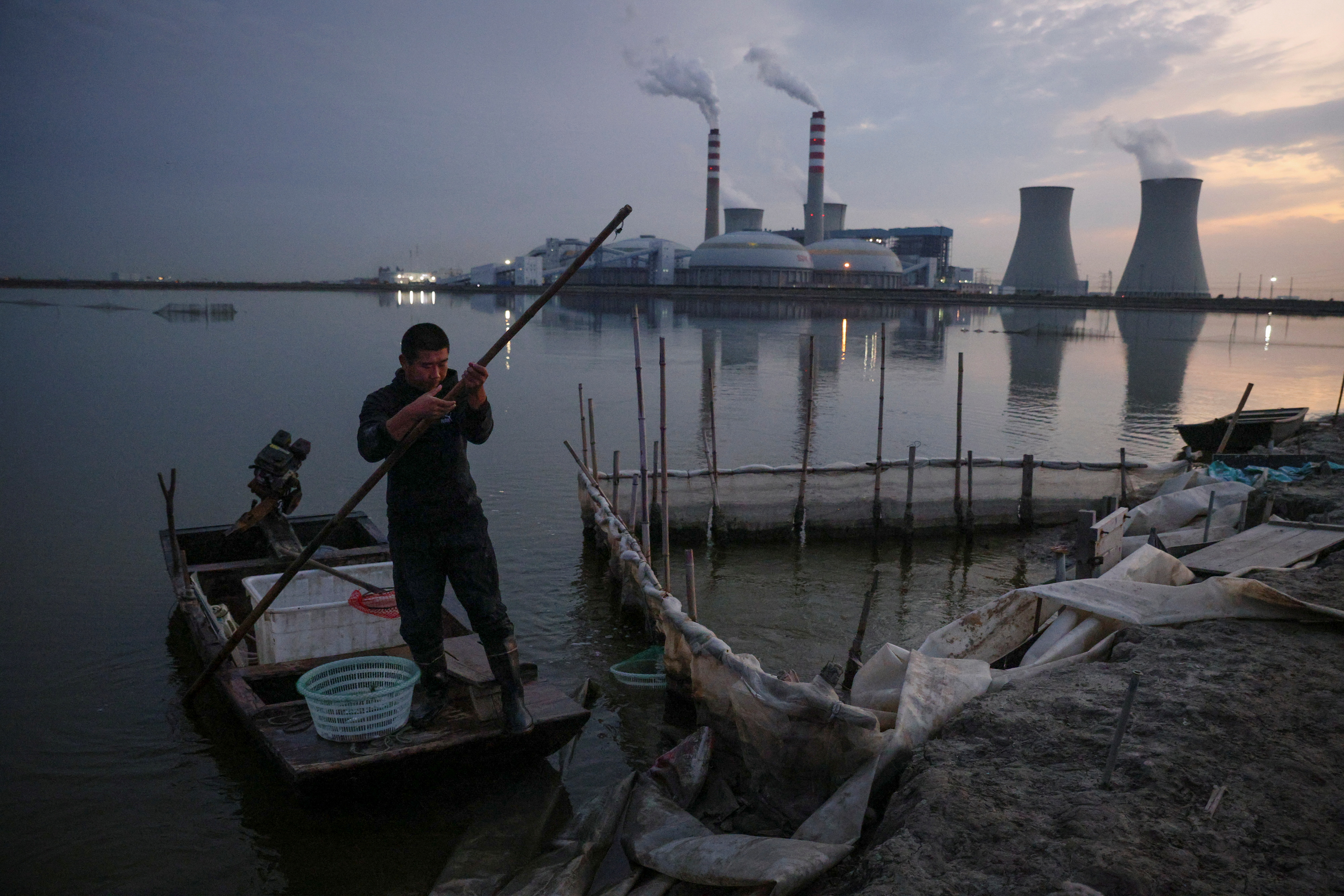 A fisherman punts a boat on a lake in front of a power plant of the State Development and Investment Corporation (SDIC) outside Tianjin, China, October 14, 2021. REUTERS/Thomas Peter