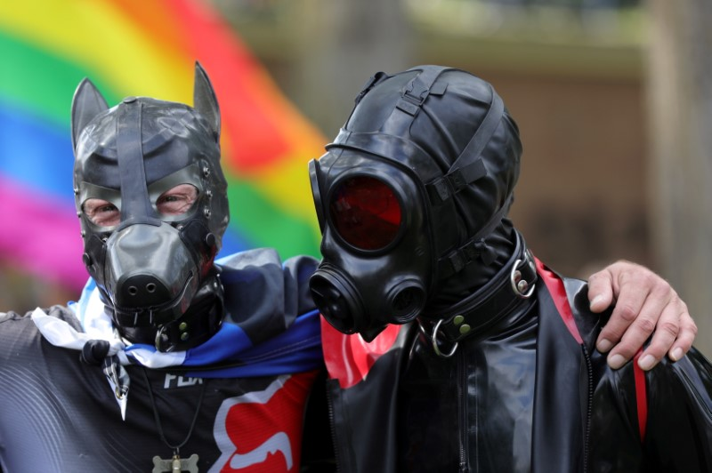Attendees in fetish gear embrace at Martin Luther King park during the 25th gay pride parade in Amsterdam, Netherlands August 7, 2021. REUTERS/Eva Plevier