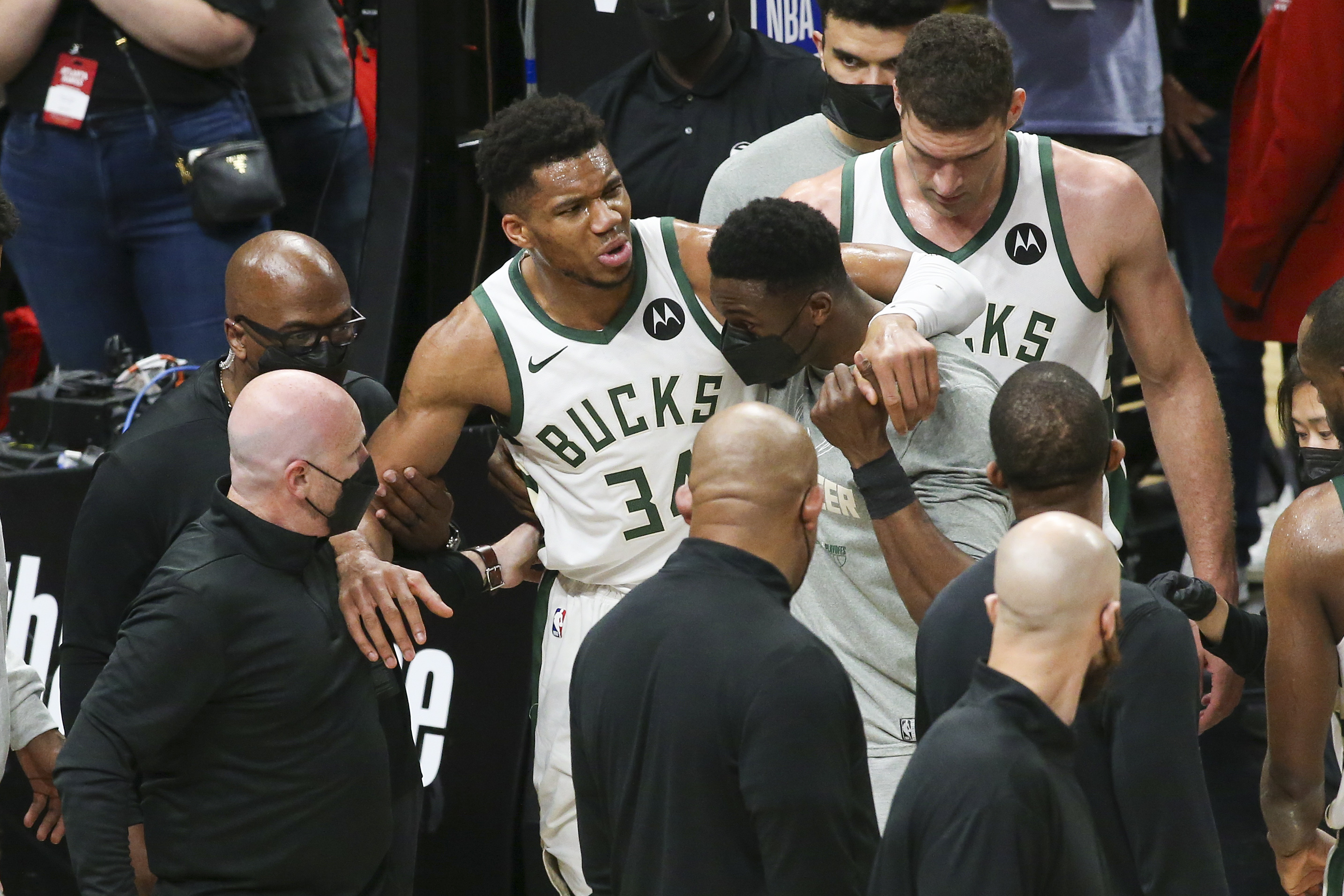 Jun 29, 2021; Atlanta, Georgia, USA; Milwaukee Bucks forward Giannis Antetokounmpo (34) is helped off the court with an injury against the Atlanta Hawks in the third quarter during game four of the Eastern Conference Finals for the 2021 NBA Playoffs at State Farm Arena. Mandatory Credit: Brett Davis-USA TODAY Sports