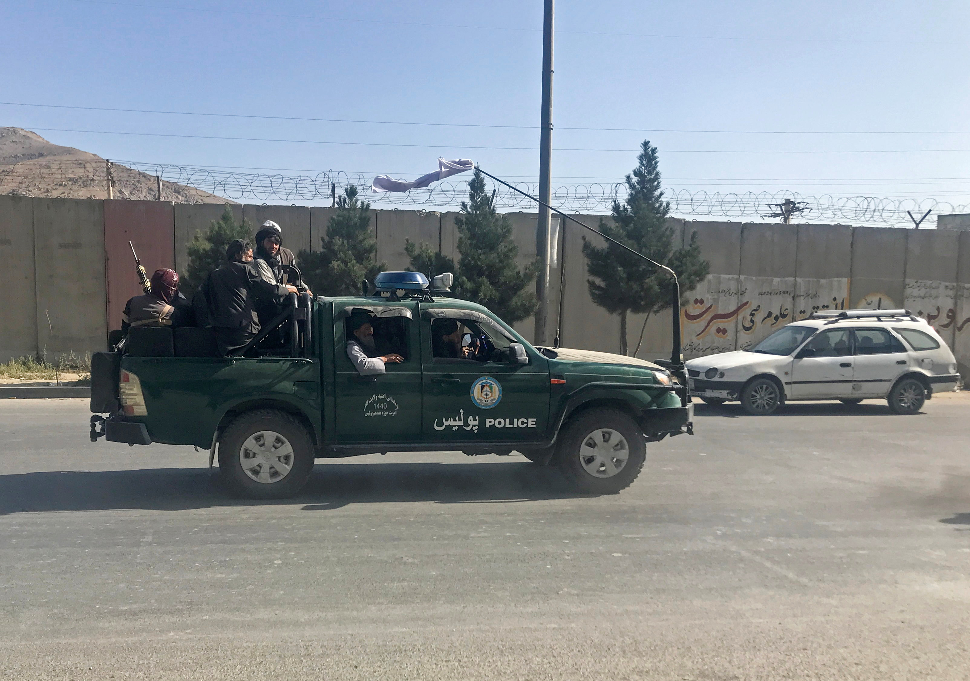 Taliban fighters ride on a police vehicle in Kabul, Afghanistan, August 16, 2021. REUTERS/Stringer