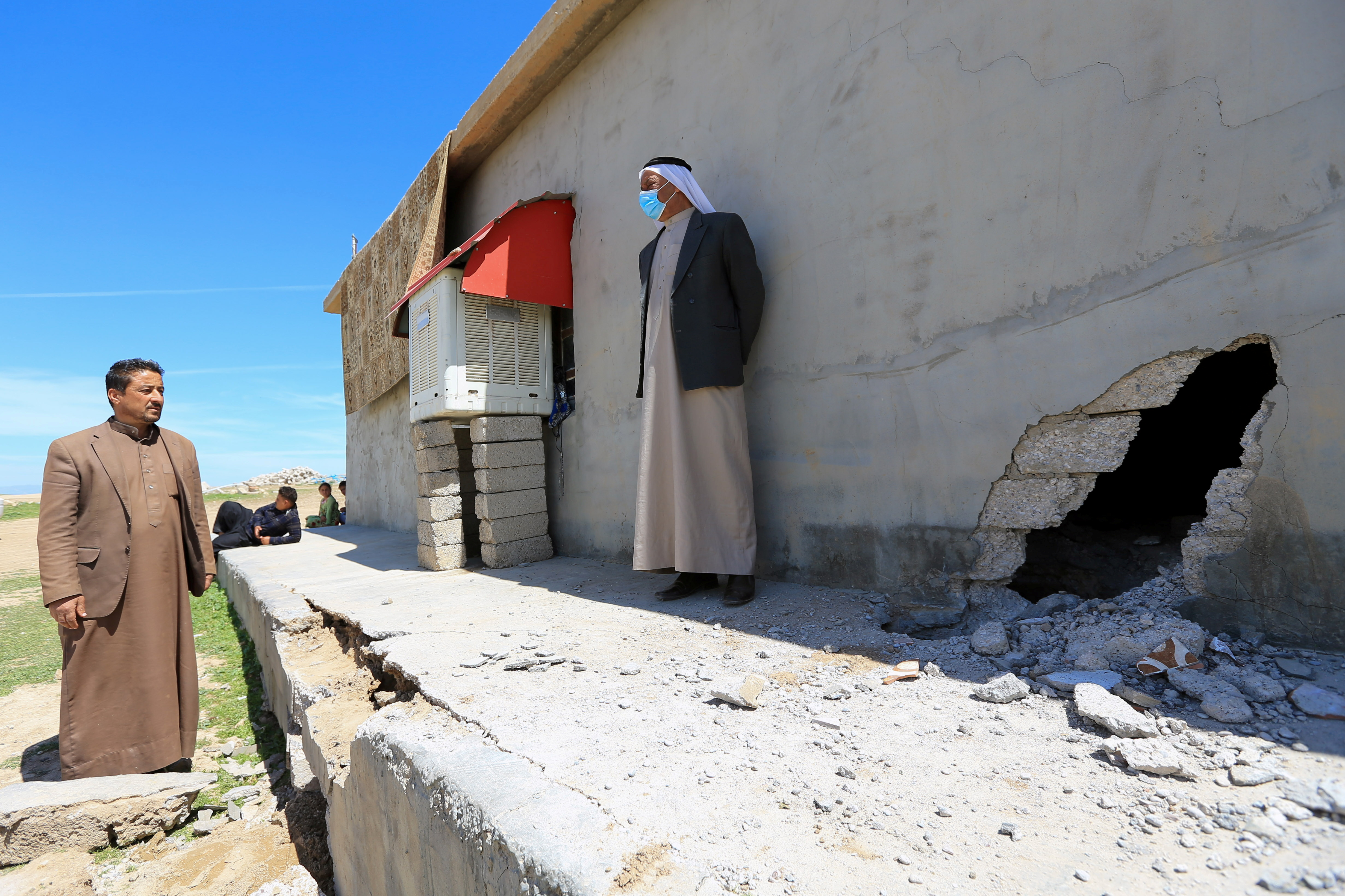 People stand next to a damaged house after a rocket attack on a military compound, at a village in Bashiqa region, Iraq, April 15, 2021. REUTERS/Ari Jalal