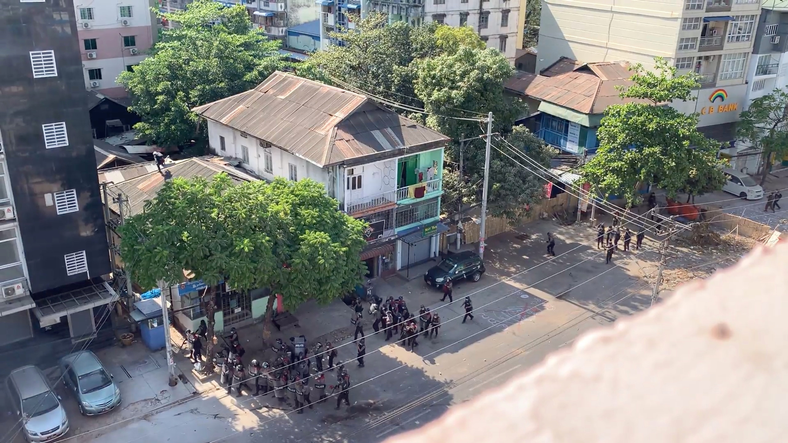A protester is seen on the roof of a building as he throws objects at police, during a protest in Yangon, Myanmar, March 4, 2021, in this still image taken from a video.  Bangkoksighseeing Facebook/via REUTERS