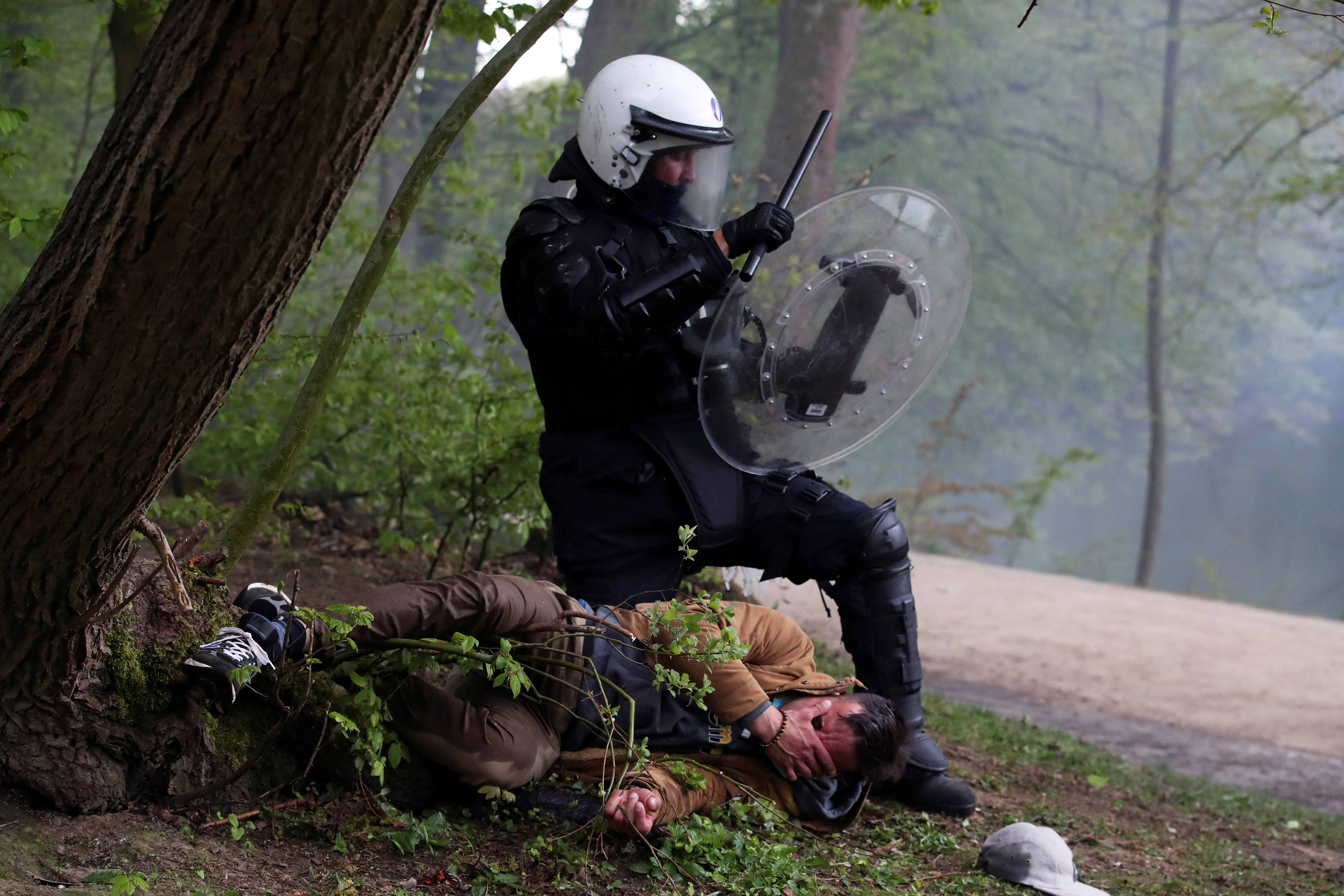 A police officer detains a man during clashes as people gather at the Bois de la Cambre/Ter Kamerenbos park for a party called
