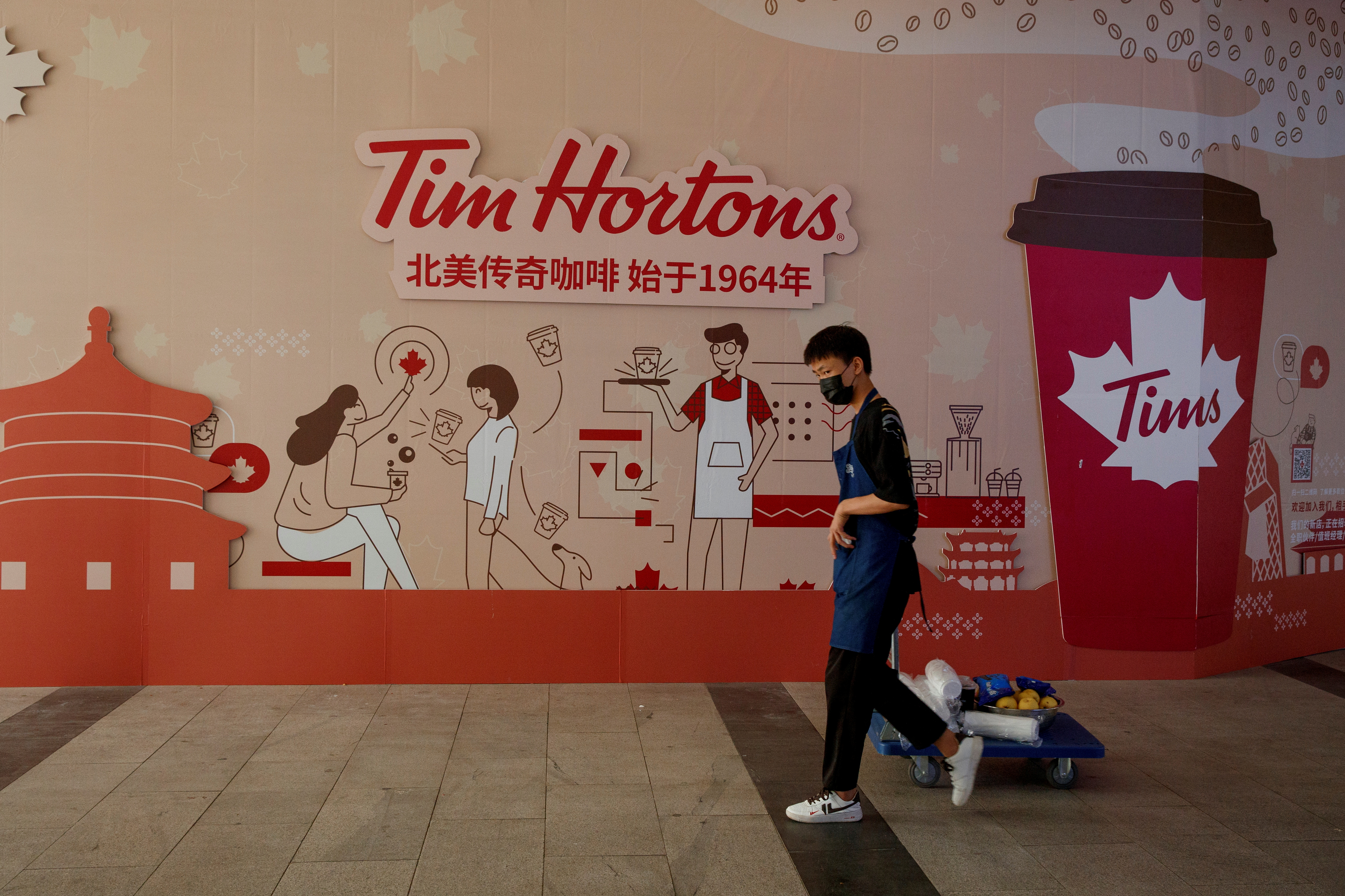 A man walks past a store front poster advertising the opening of a cafe of the Canadian coffee and fast food chain Tim Hortons in Beijing, China, July 6, 2020.  REUTERS/Thomas Peter/File Photo