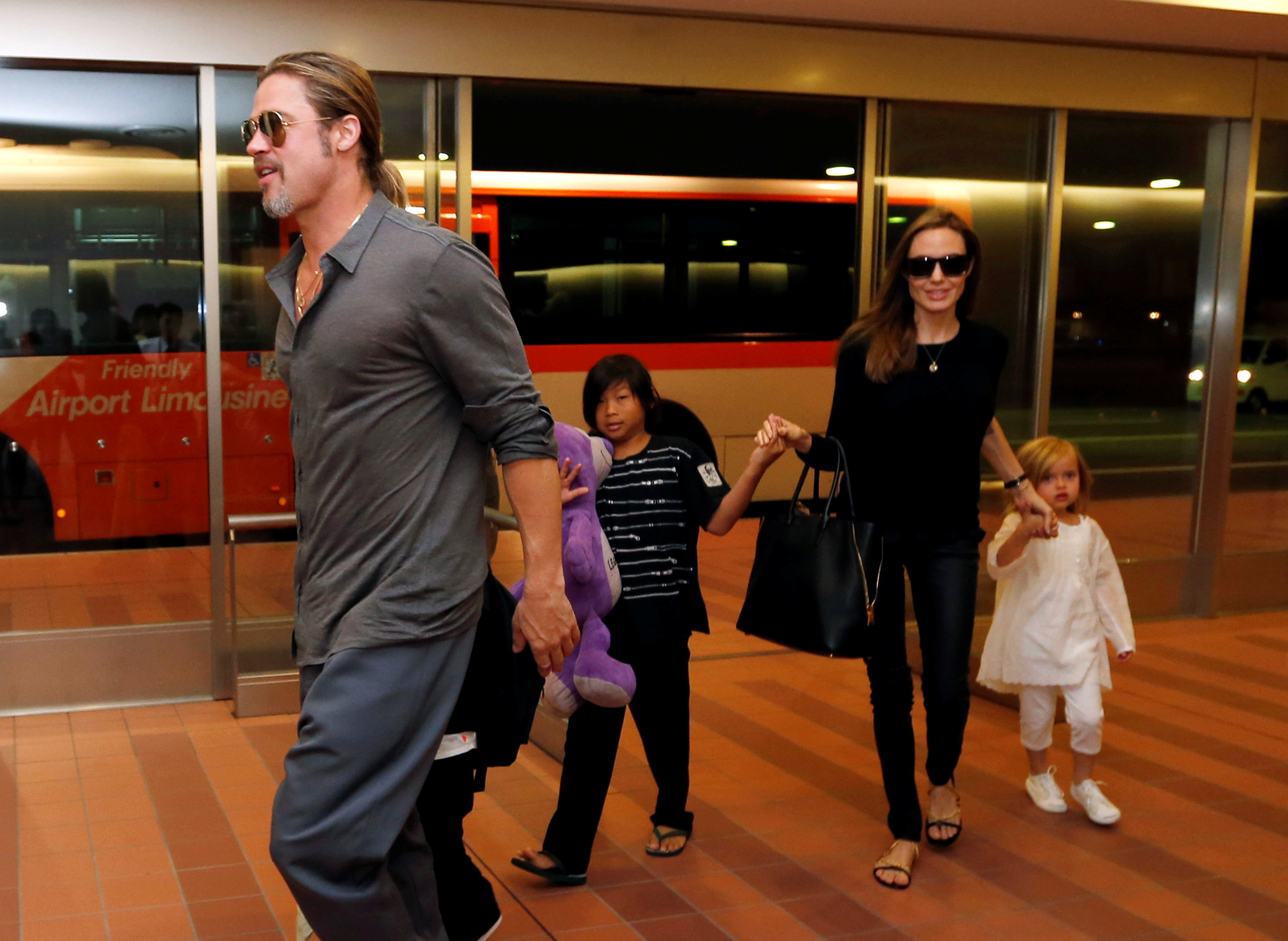 Hollywood actors Brad Pitt (L) and actress Angelina Jolie (2nd R) arrive with their children Knox (beside Pitt), Vivienne (R) and Pax (C) at Haneda international airport in Tokyo, Japan on July 28, 2013.  REUTERS/Issei Kato/File Photo/File Photo