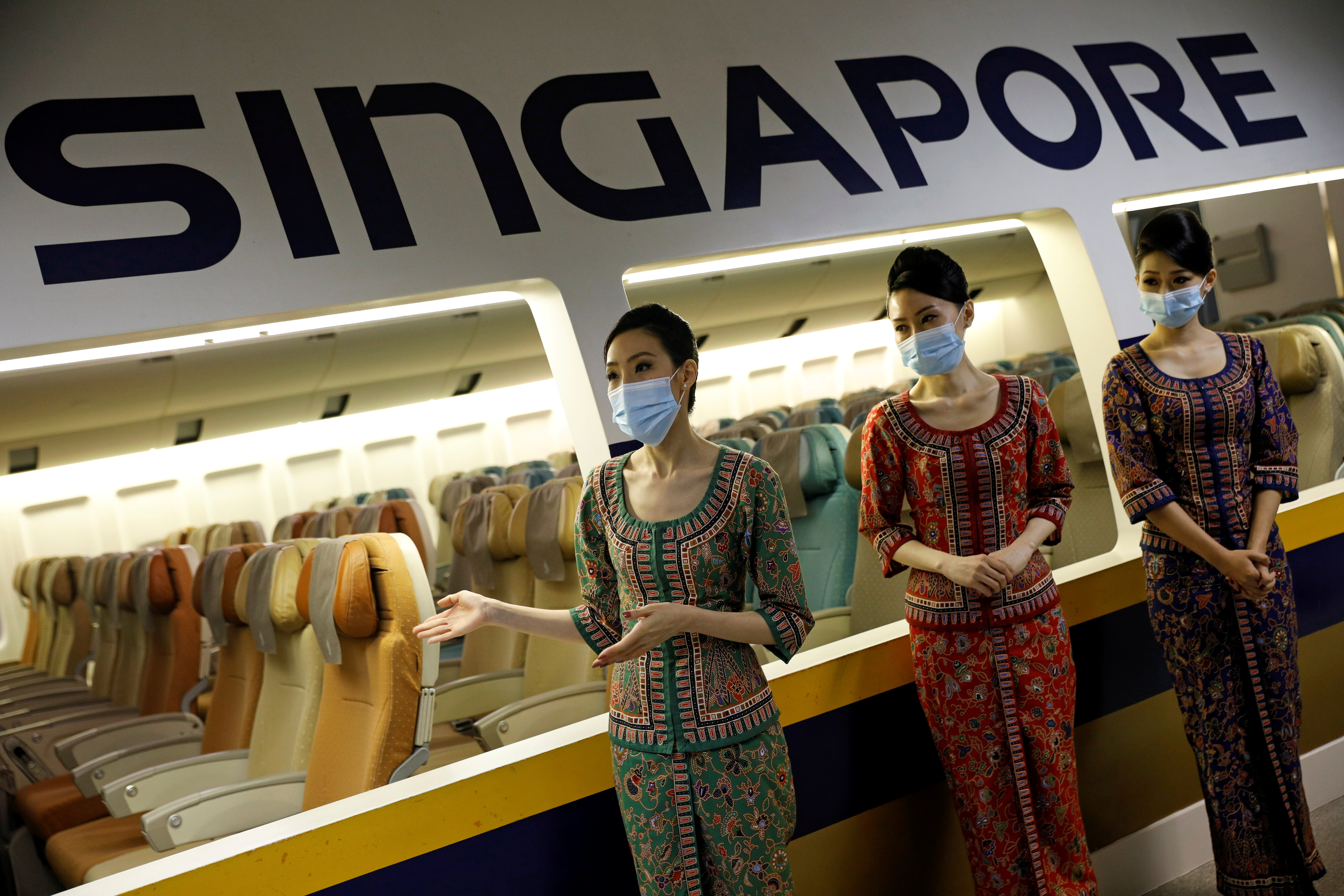 Cabin crew speak to participants during a tour of the Singapore Airlines Training Centre in Singapore November 21, 2020, as part of a series of initiatives to re-engage customers who have not been able to travel due to the coronavirus.  REUTERS/Edgar Su/File Photo