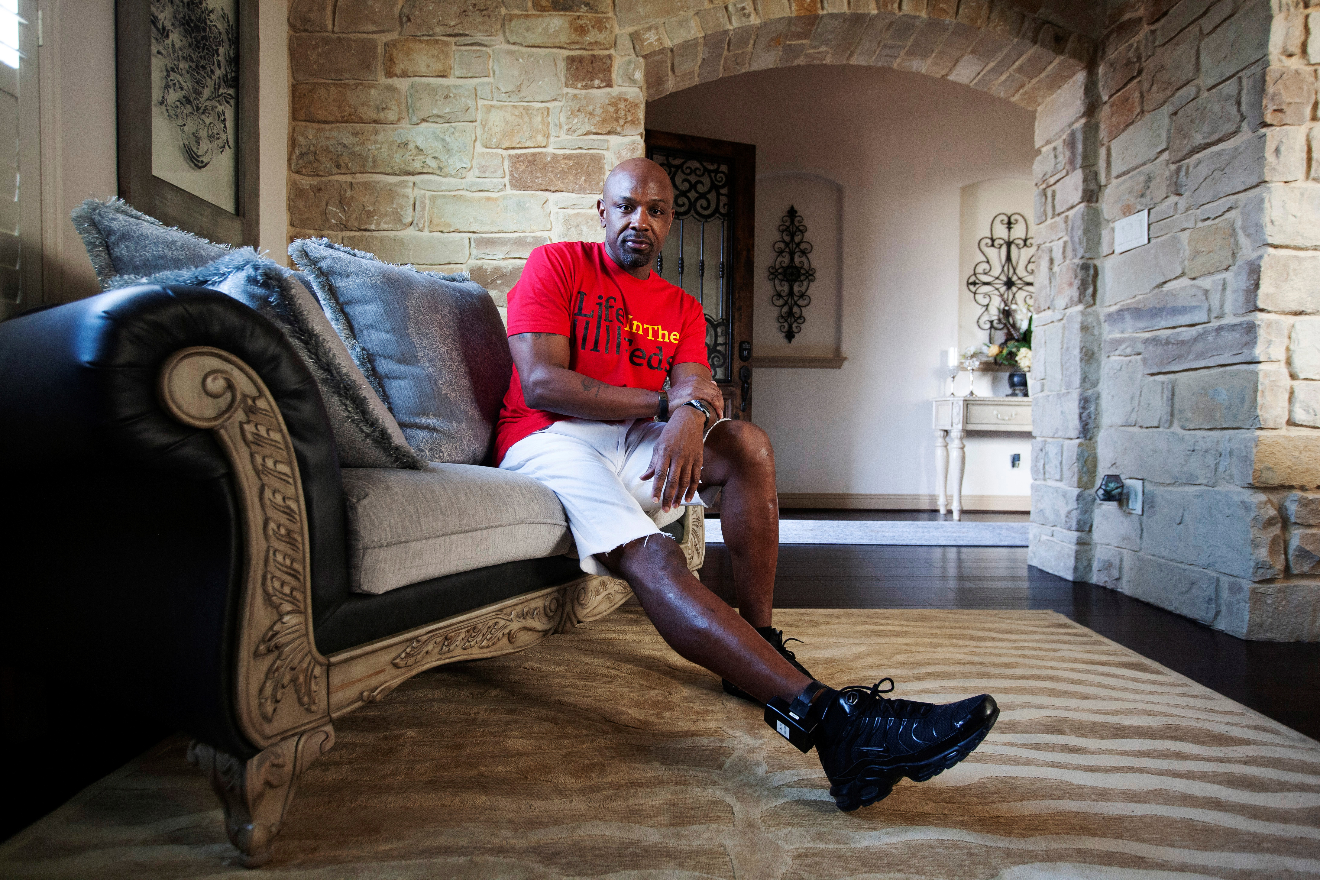 Kendrick Fulton, who was released to home confinement due to the coronavirus disease (COVID-19) pandemic, poses for a photo at his sister's house in Round Rock, Texas, U.S., April 8, 2021. He is wearing an ankle monitor that he must charge nightly in order to comply with the terms of his release. REUTERS/Nuri Vallbona