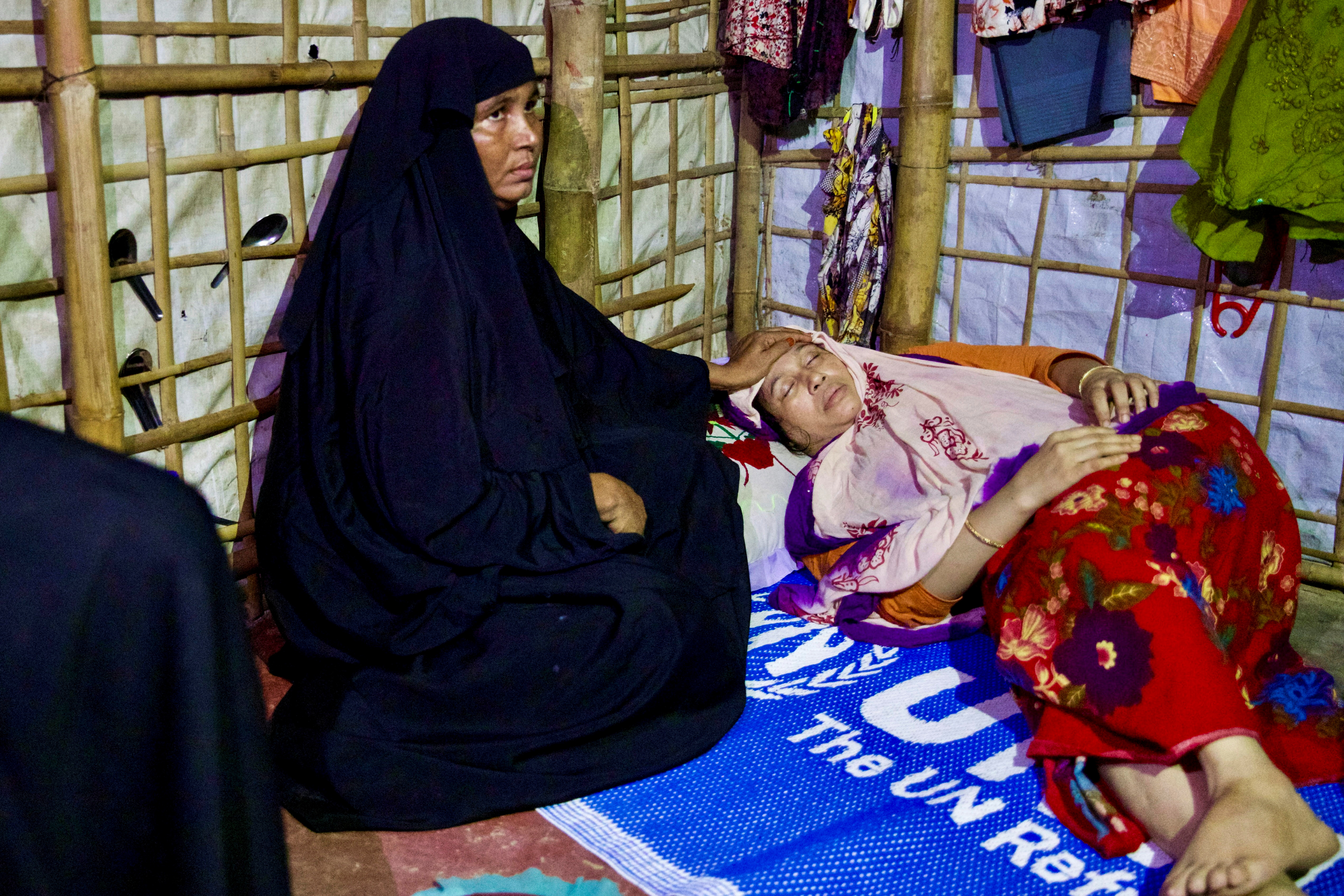 Nasima, the wife of the Rohingya Muslim leader, is surrounded by relatives at her shelter in Kutupalang camp, in Cox's Bazar, Bangladesh, September 30, 2021. REUTERS/Mushfiqul Alam