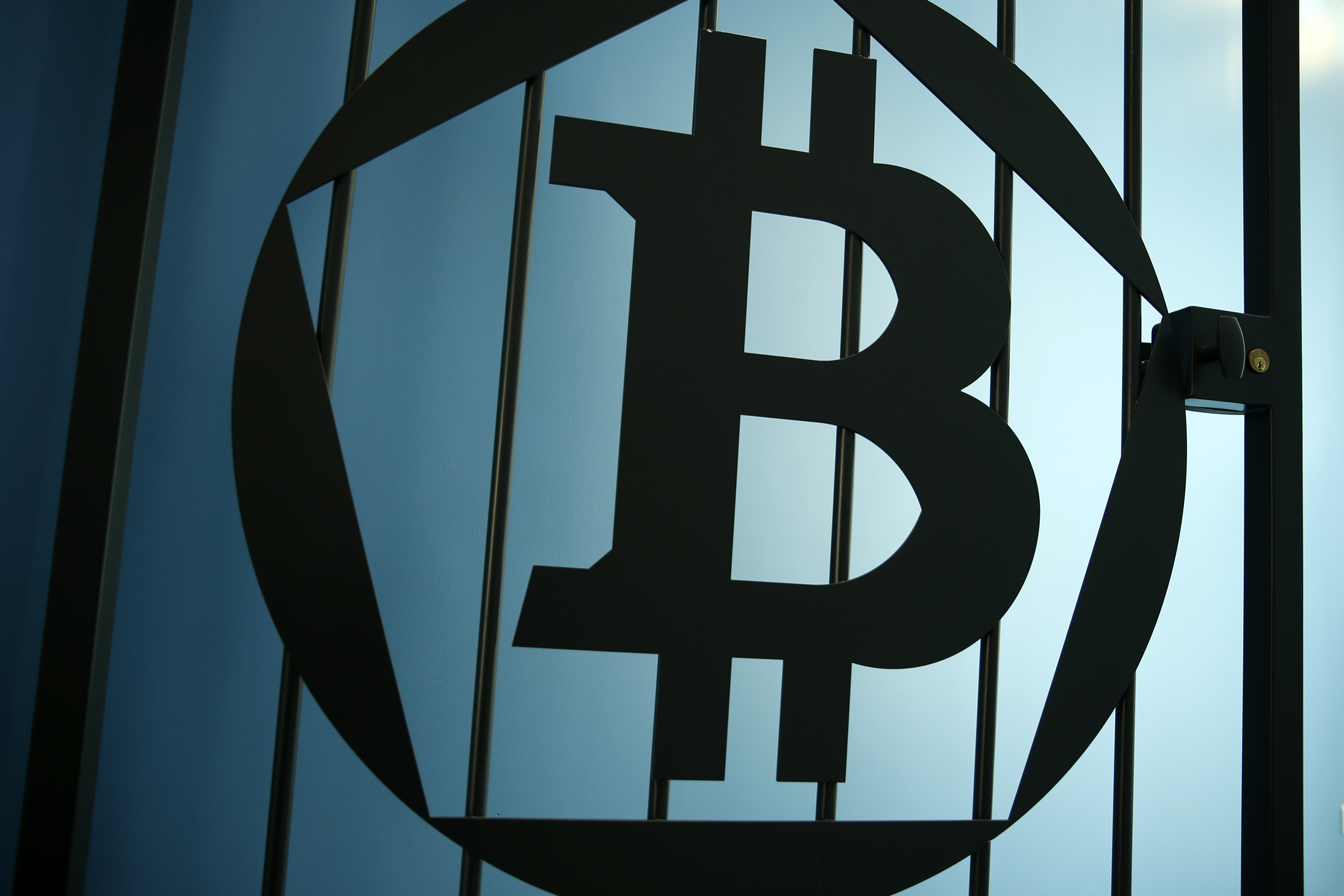 A Bitcoin (virtual currency) logo is pictured on a door in an illustration picture taken at La Maison du Bitcoin in Paris May 27, 2015. British authorities have come out in support of digital currencies in the name of promoting financial innovation, while proposing that regulations should be drawn up to prevent their use in crime. But it is technophiles who are leading the drive to make London a real-world hub for trade in web-based