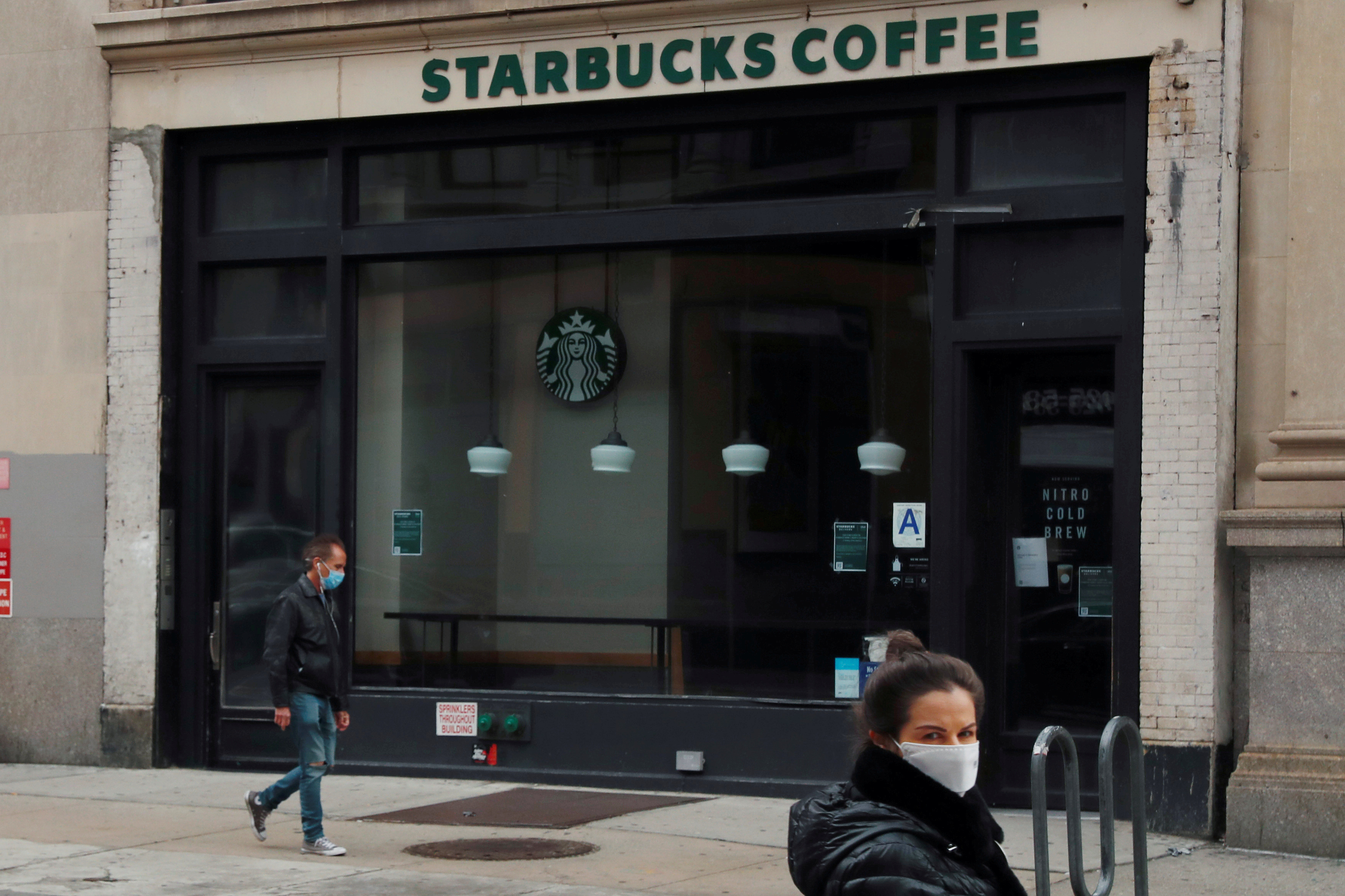 A man wearing a mask walks in front of a shuttered Starbucks as the spread of the coronavirus disease (COVID-19) outbreak continues in the Manhattan borough of New York City, U.S., April 27, 2020. REUTERS/Lucas Jackson