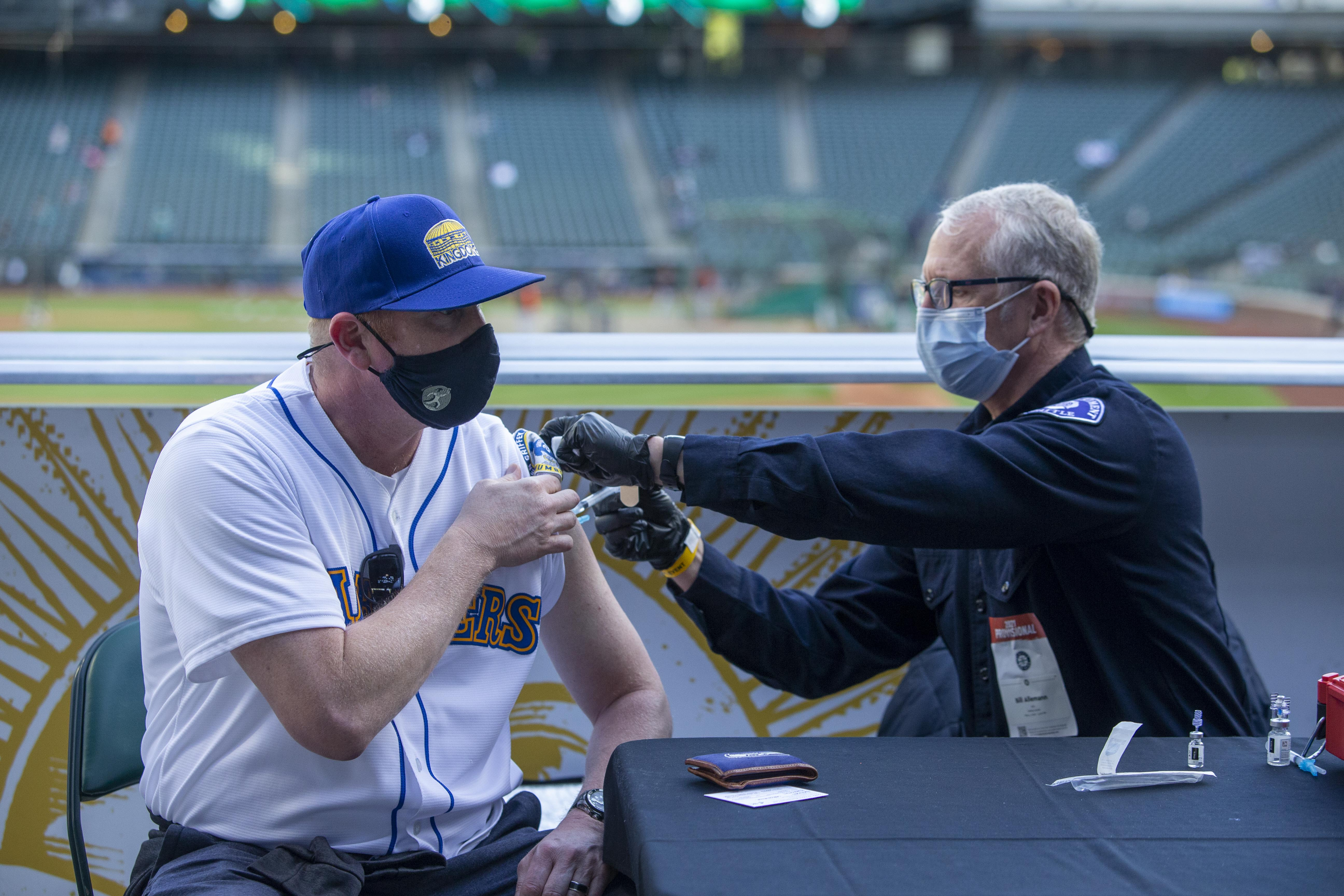 May 4, 2021; Seattle, Washington, USA; Seattle Fire Department EMT Bill Allemann gives Chris Hoffman, of Kent, Washington a Johnson & Johnson Covid-19 vaccine during batting practice before a game between the Seattle Mariners and Baltimore Orioles at T-Mobile Park. Mandatory Credit: Joe Nicholson-USA TODAY Sports
