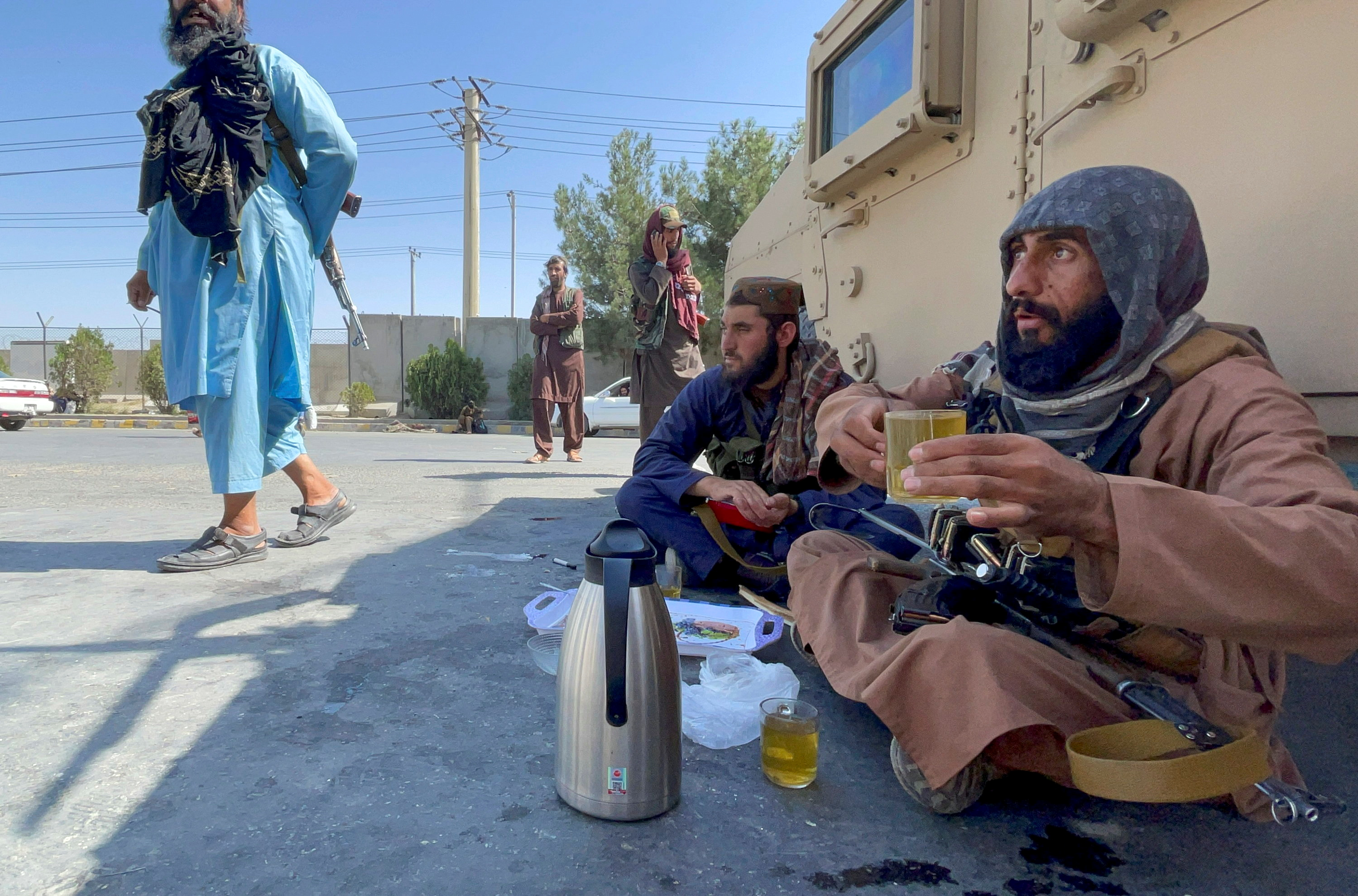 Armed Taliban men drink tea as Taliban forces block the roads around the airport after yesterday's explosions in Kabul, Afghanistan August 27, 2021. REUTER/Stringer