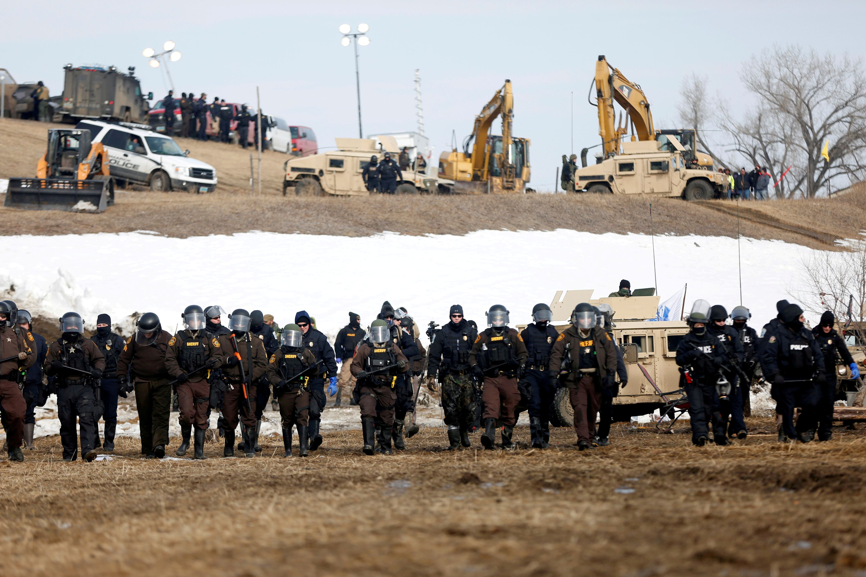 Law enforcement officers advance into the main opposition camp against the Dakota Access oil pipeline near Cannon Ball, North Dakota, U.S., February 23, 2017. REUTERS/Terray Sylvester/File Photo