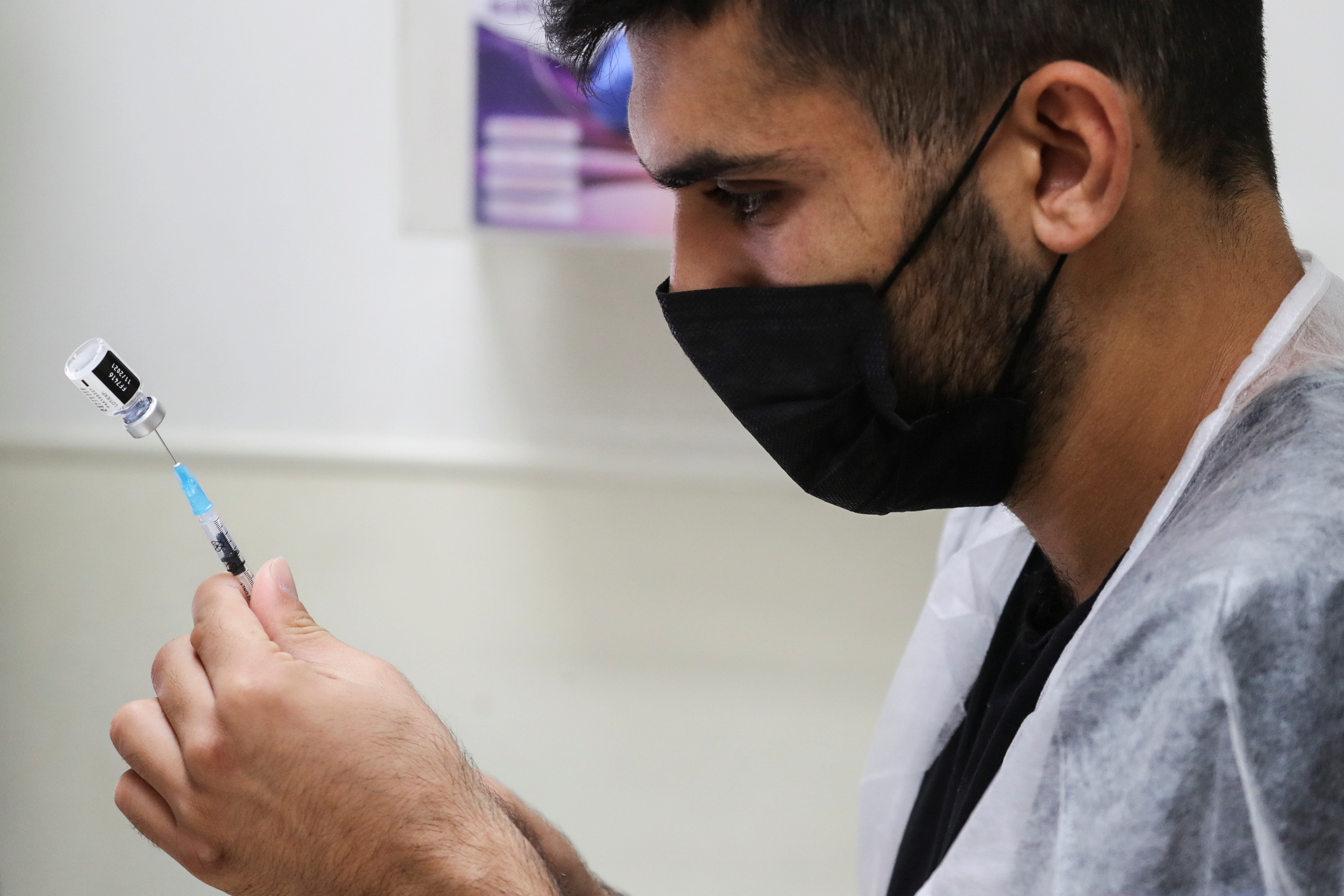 A medical worker prepares to administer a patient's third dose of the coronavirus disease (COVID-19) vaccine as country launches booster shots for over 40-year-olds, in Jerusalem August 20, 2021. REUTERS/Ammar Awad