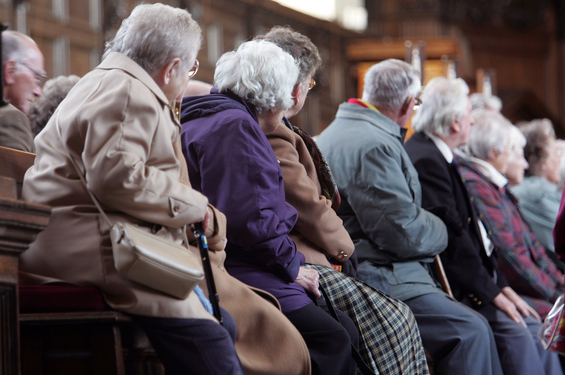 Elderly people listen to a tour guide in a church in central London, November 29, 2005. REUTERS/Toby Melville/Files