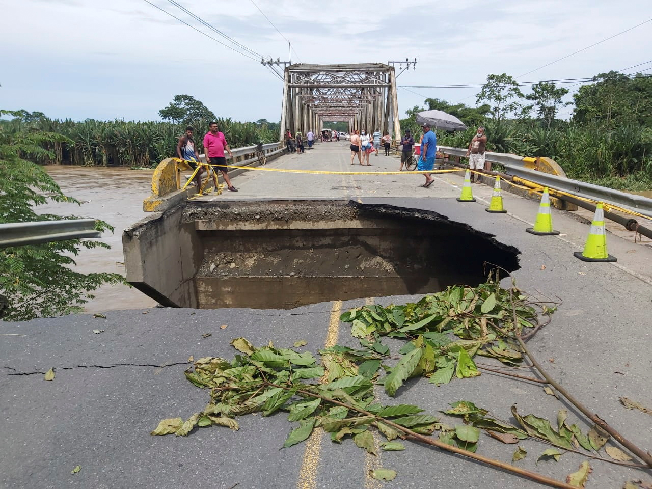 People stand on a bridge over La Estrella river damaged by floods due to heavy rains, in Limon, Costa Rica July 26, 2021. Costa Rica's Presidency/Handout via REUTERS