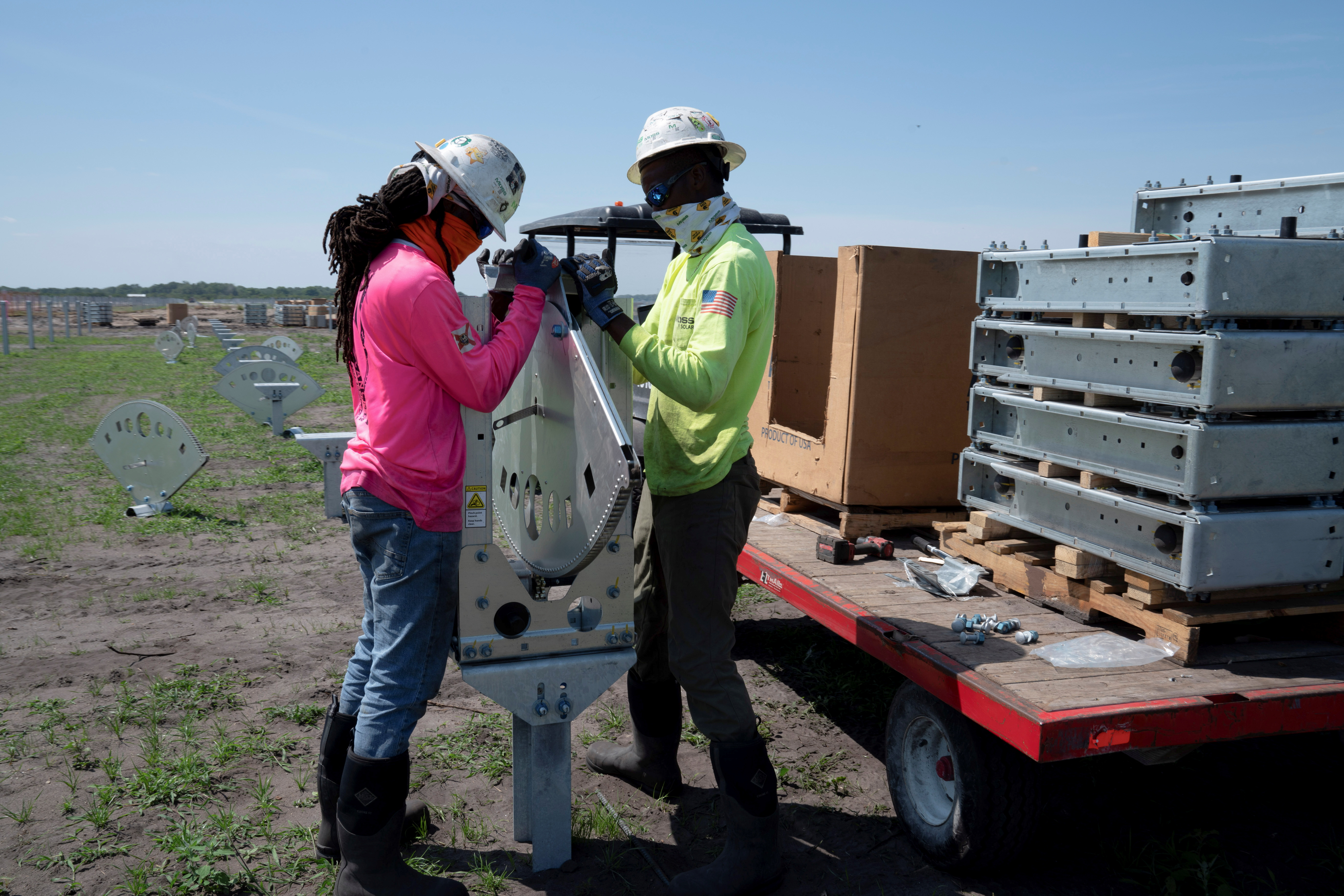 Construction workers Tekovin Miller and Darien Bailey install actuators for tilting panels at the Duette solar site which is being developed on previously agricultural land in Bowling Green, Florida, U.S., March 24, 2021.  REUTERS/Dane Rhys